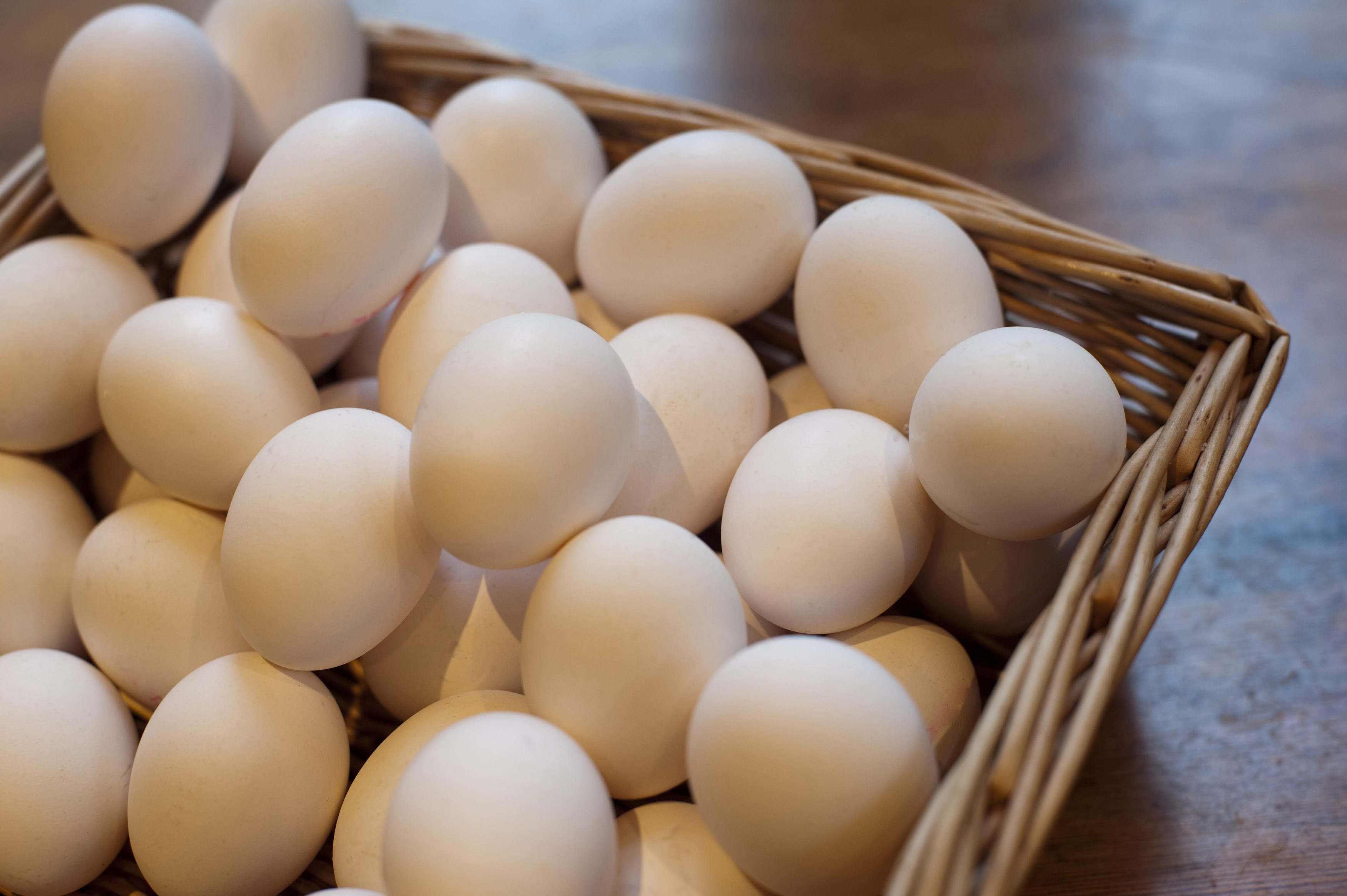 Farm fresh hens eggs displayed in a wicker basket at a farmers market for a healthy breakfast or to use as an ingredient in cooking and baking