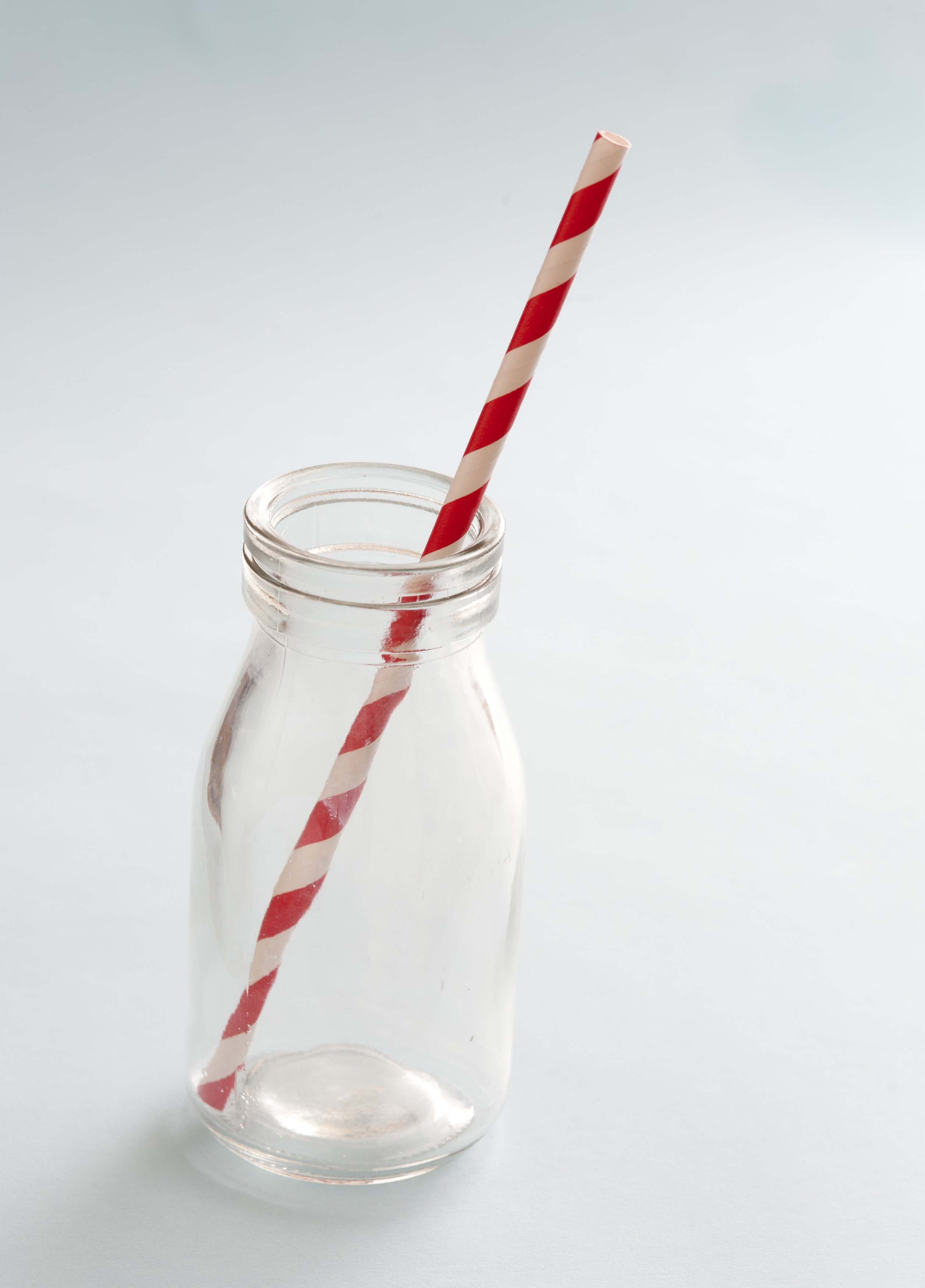 Empty kids glass milk bottle with striped red and white plastic straw over a white background with copy space