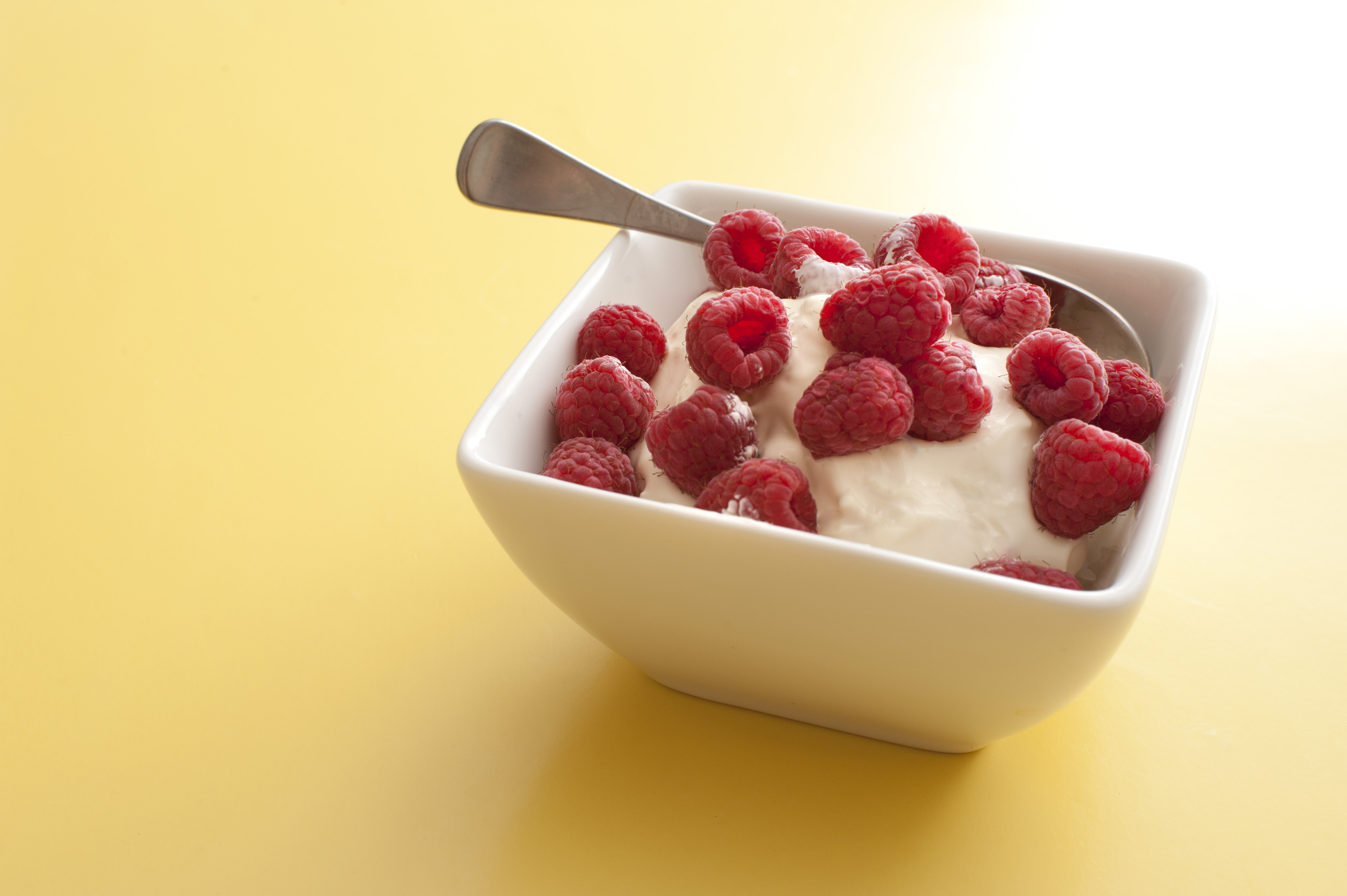 Delicious creamy yoghurt topped with fresh red raspberries served in a modern square bowl over a yellow background with copy space