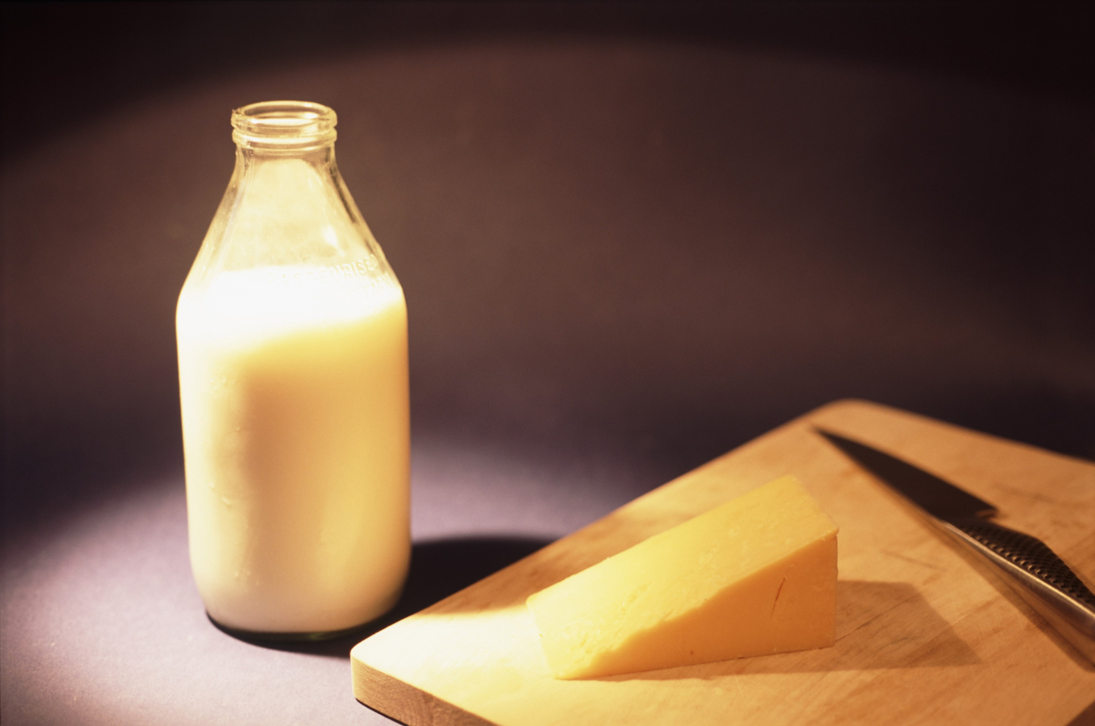 Glass bottle of fresh cows milk standing alongside a wedge of cheddar cheese on a cheeseboard against a dark background with copyspace