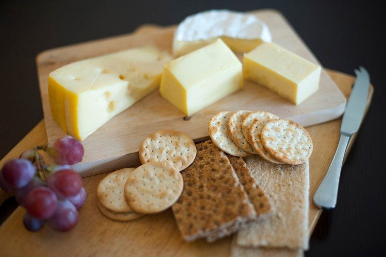 Cheese and biscuit platter with portions of assorted cheeses, crackers ...