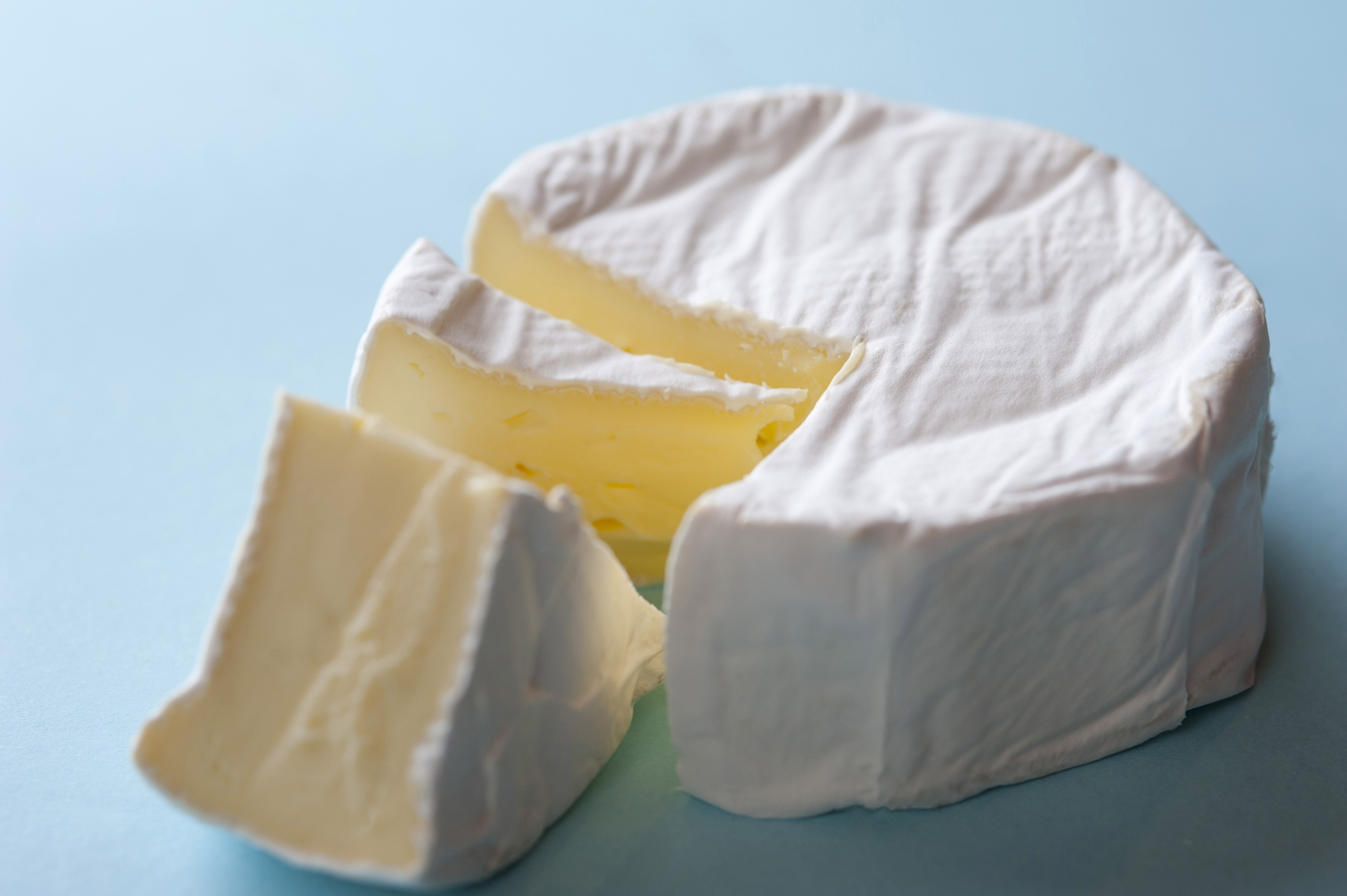 Round soft brie cheese with a wedge removed, closeup high angle view