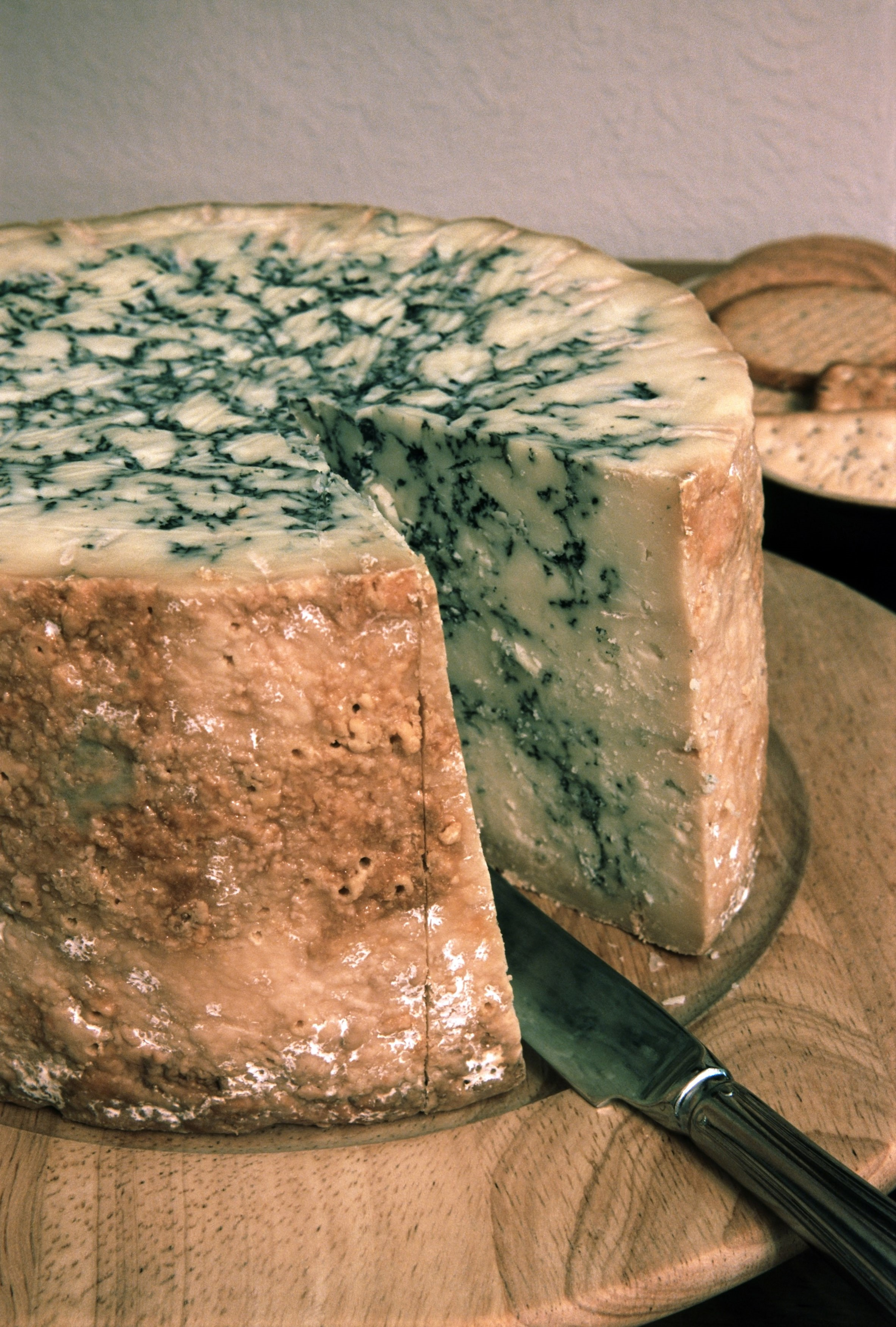Stilton cheese, an English blue veined cheese made with added cream which has a distinctive flavour and high fat content, closeup view of a wheel with a wedge removed