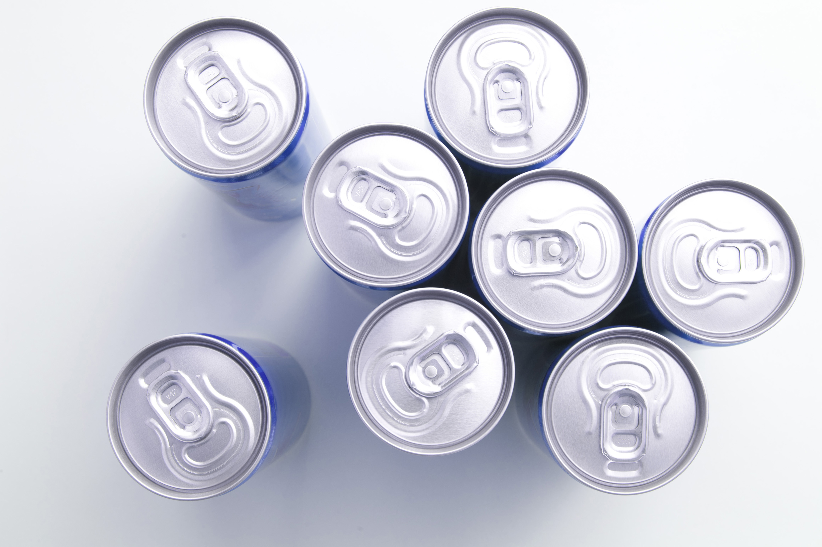 Unopened drinks cans viewed from above looking down onto the aluminium lids over a white background