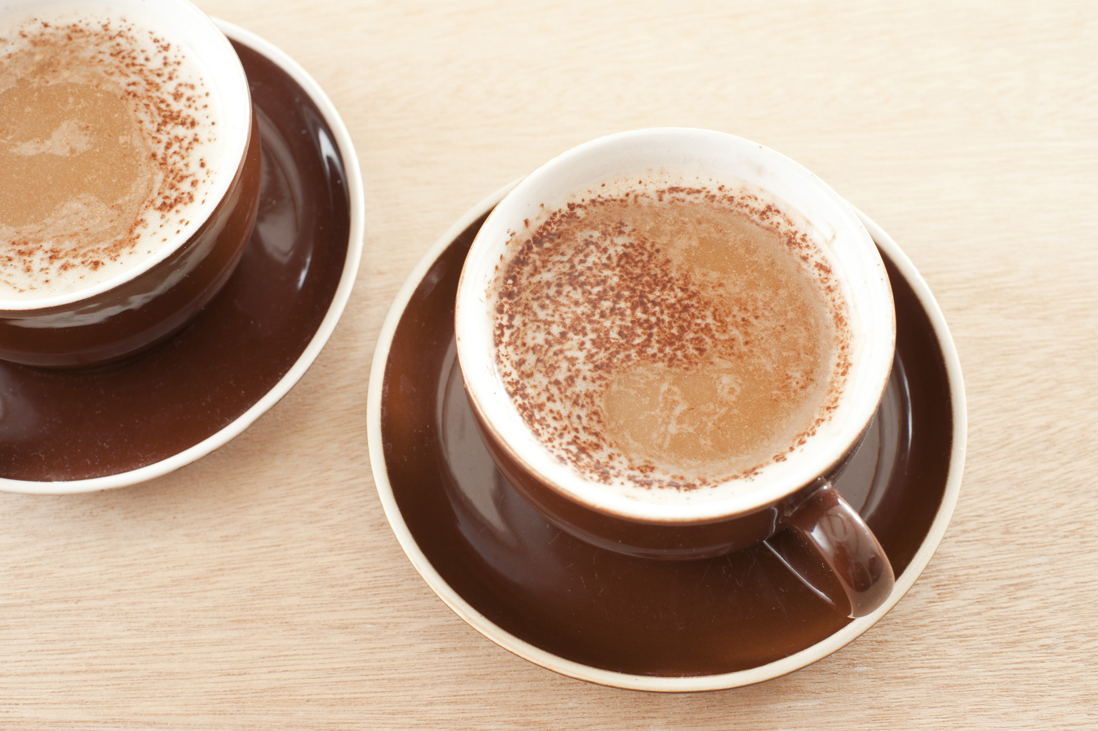 Two cups of freshly brewed aromatic frothy cappuccino in brown cups and saucers viewed high angle on yellow