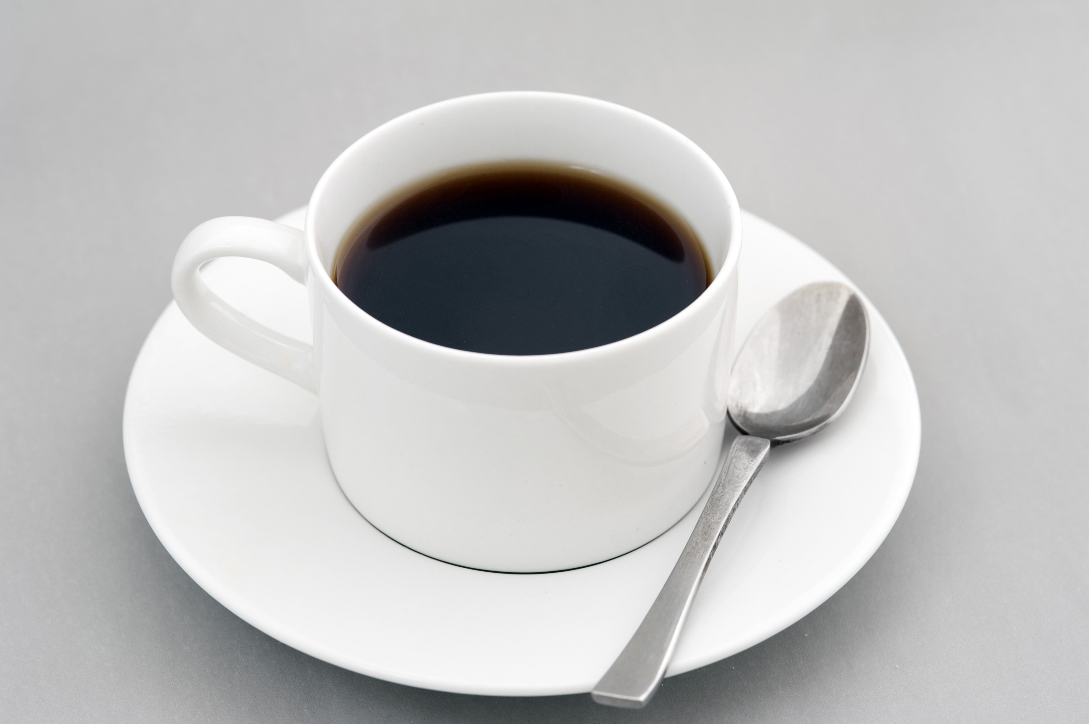 Cup of strong black espresso coffee served in a generic white ceramic cup and saucer with teaspoon over a grey background