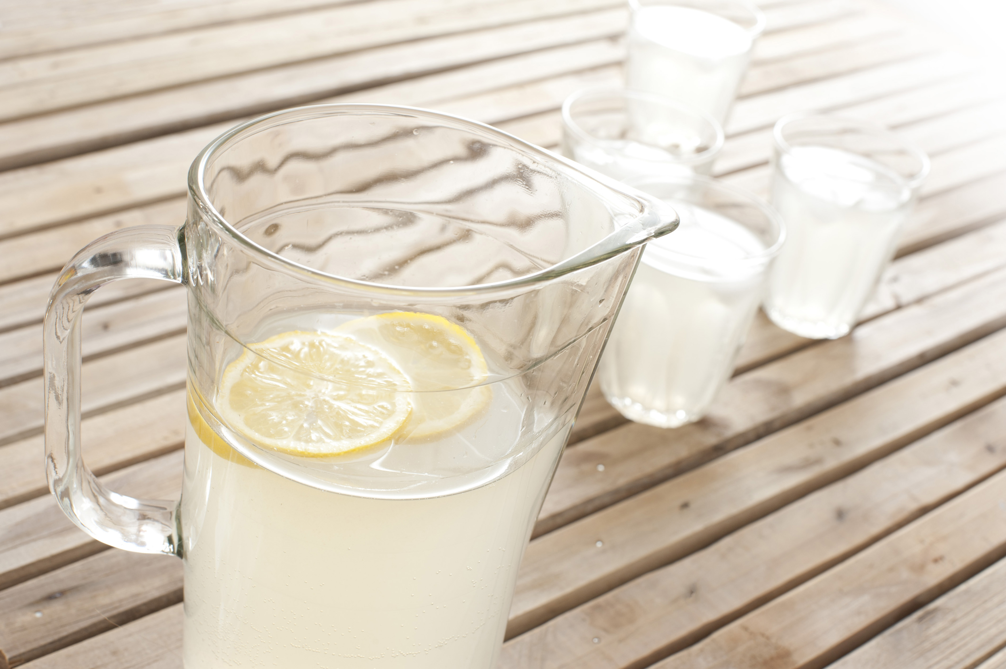 Fresh homemade lemonade in a jug with full glasses on an outdoor wooden picnic table for a refreshing summer beverage, high angle view