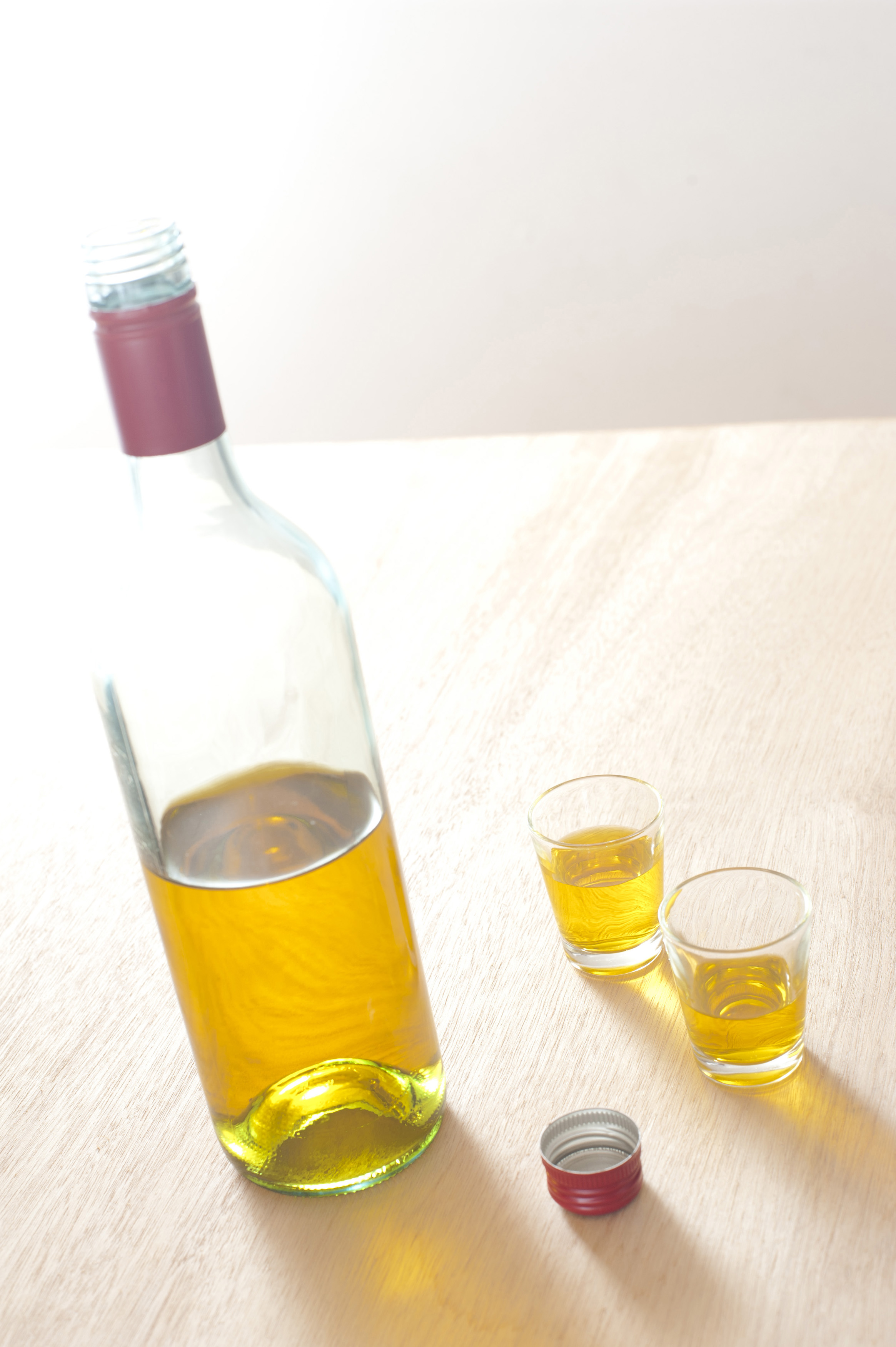 Close up Unlabled Bottle and Glasses of Yellow Wine on Top of a Wooden Table