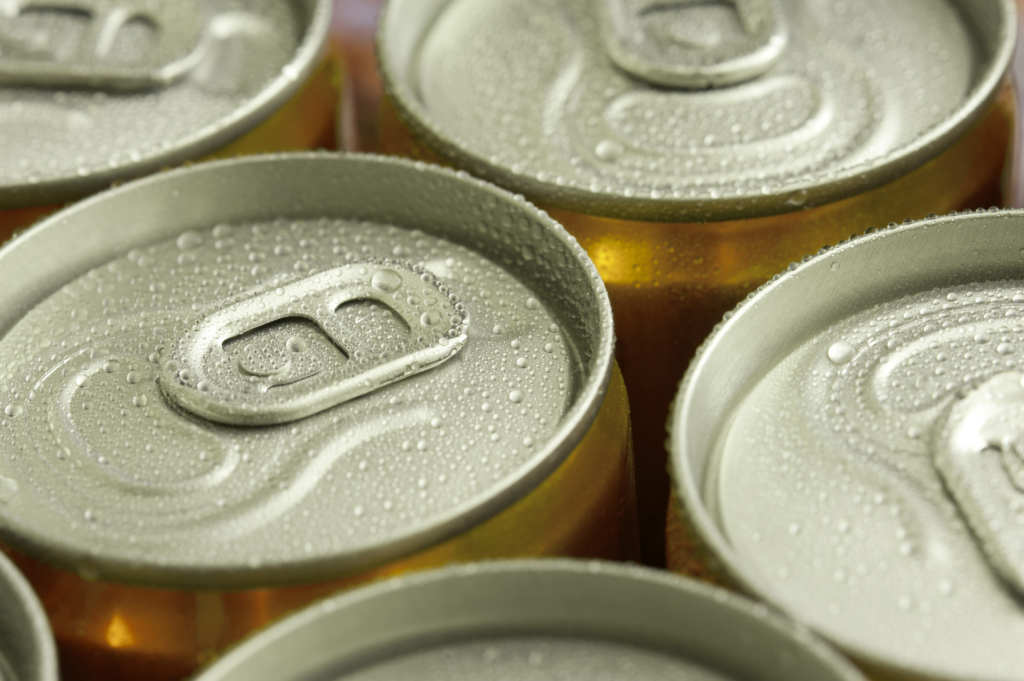 Close up of the tops of rows of unopened ice cold cans of drink with moisture condensation in a full frame background