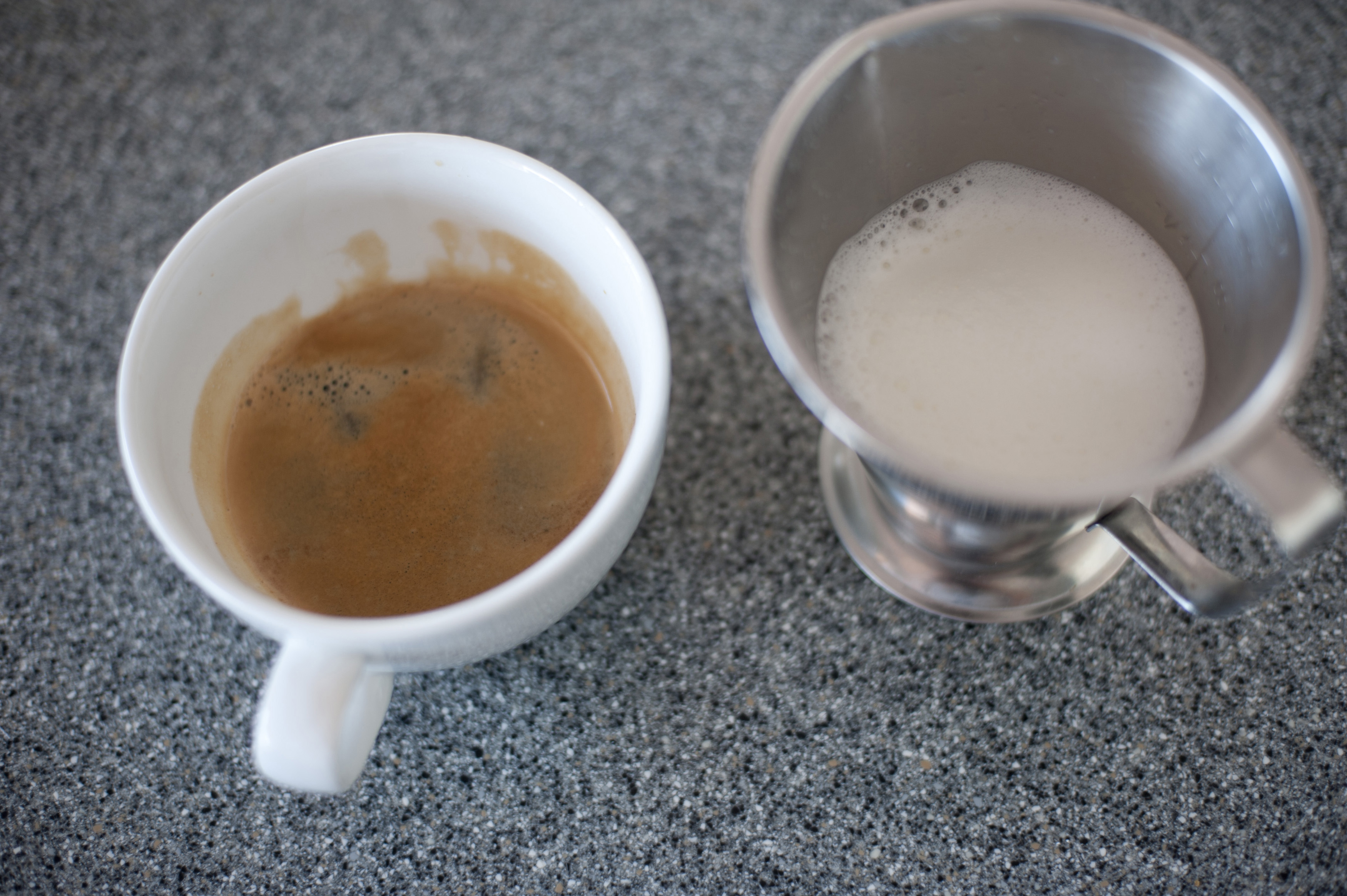 Cup of strong espresso coffee with frothy heated milk alongside in a metal container from a coffee machine, high angle view on a dark grey background