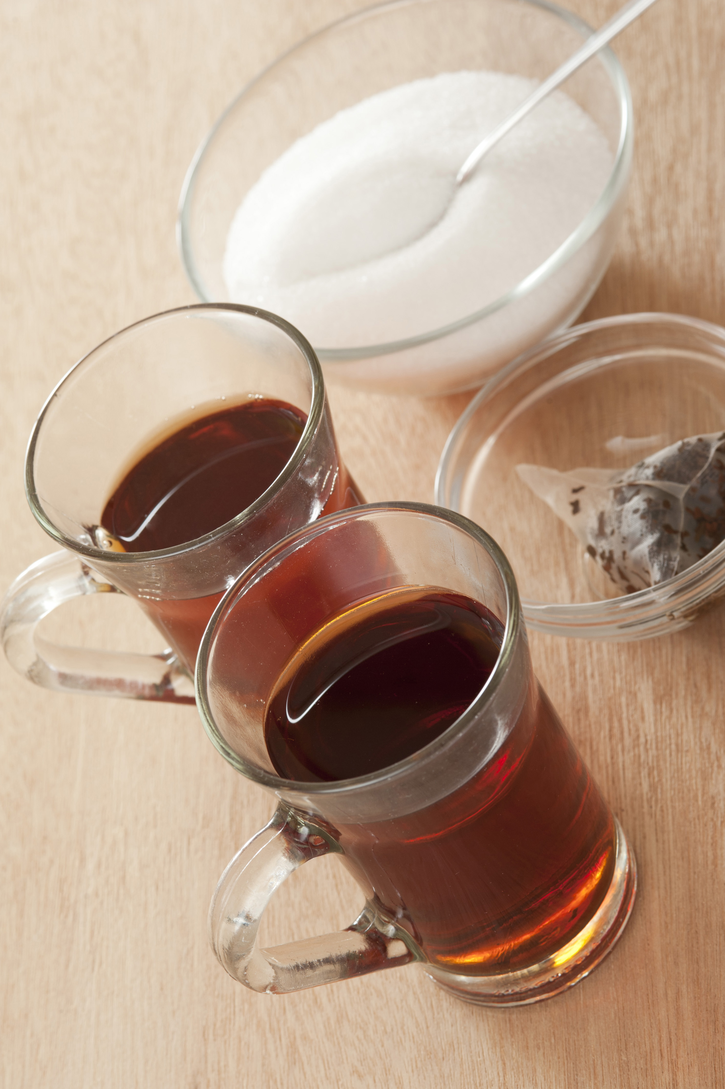 Two cups of hot sweet black tea in glass mugs viewed high angle on a wooden table with the sugar bowl behind and used teabags in a dish