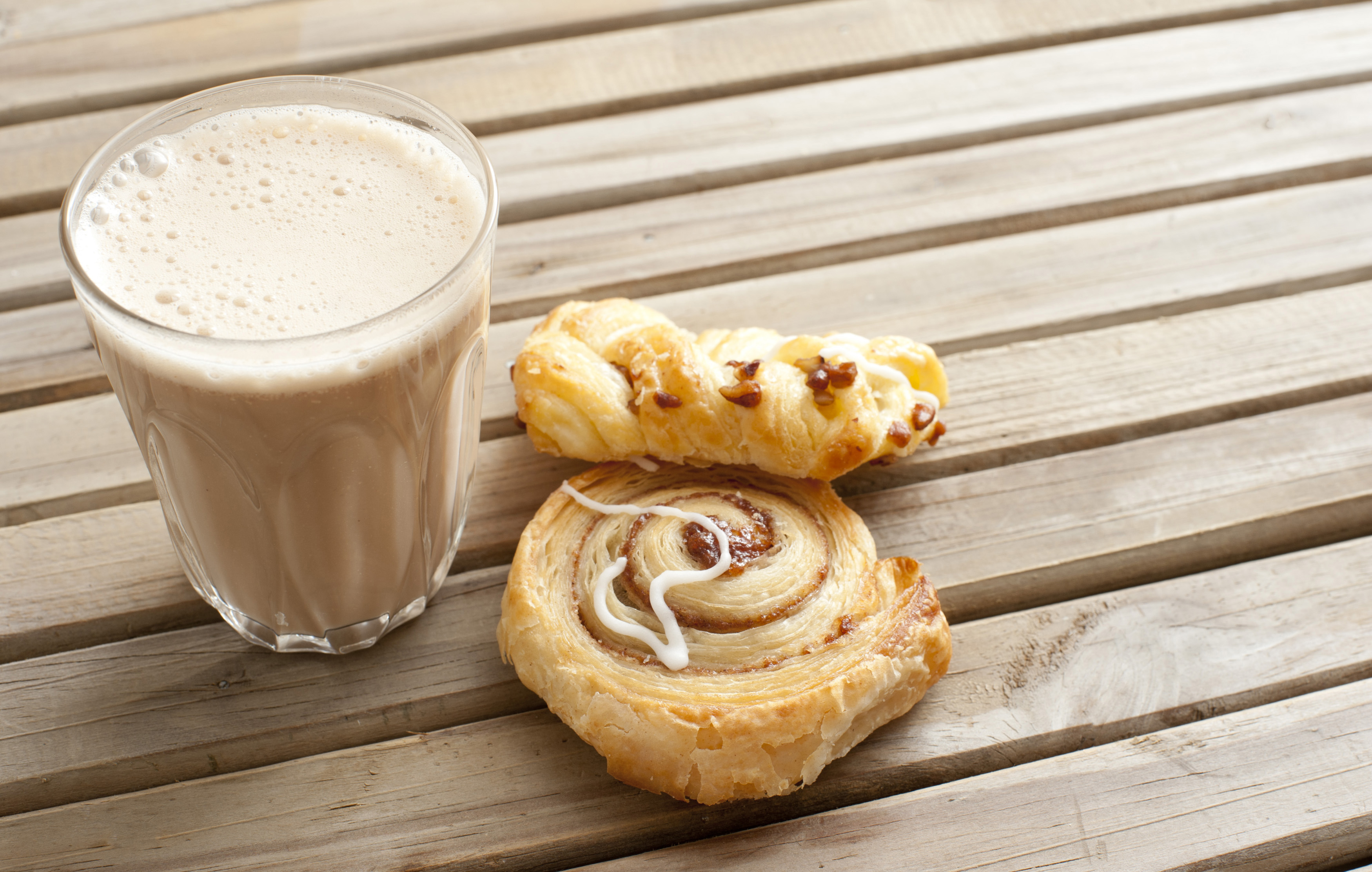 Latte coffee with fresh apple and cinnamon Danish pastries standing outdoors on a wooden garden table for an early morning snack