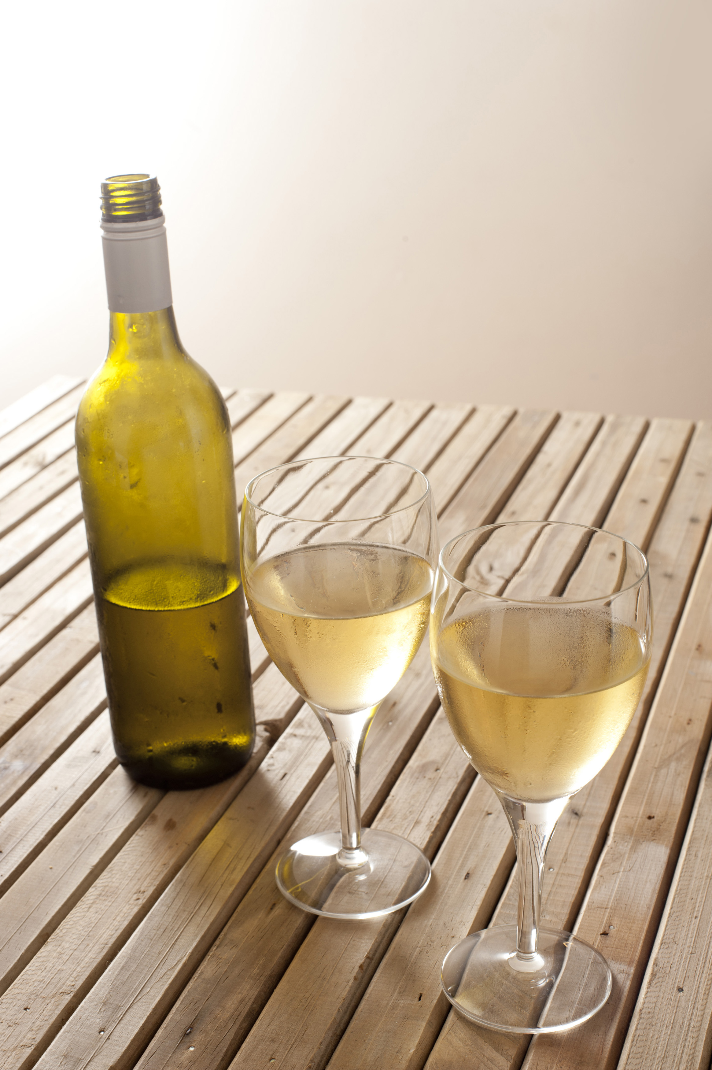 Open unlabelled white wine bottle with two full glasses of wine on a slatted wooden table with copyspace
