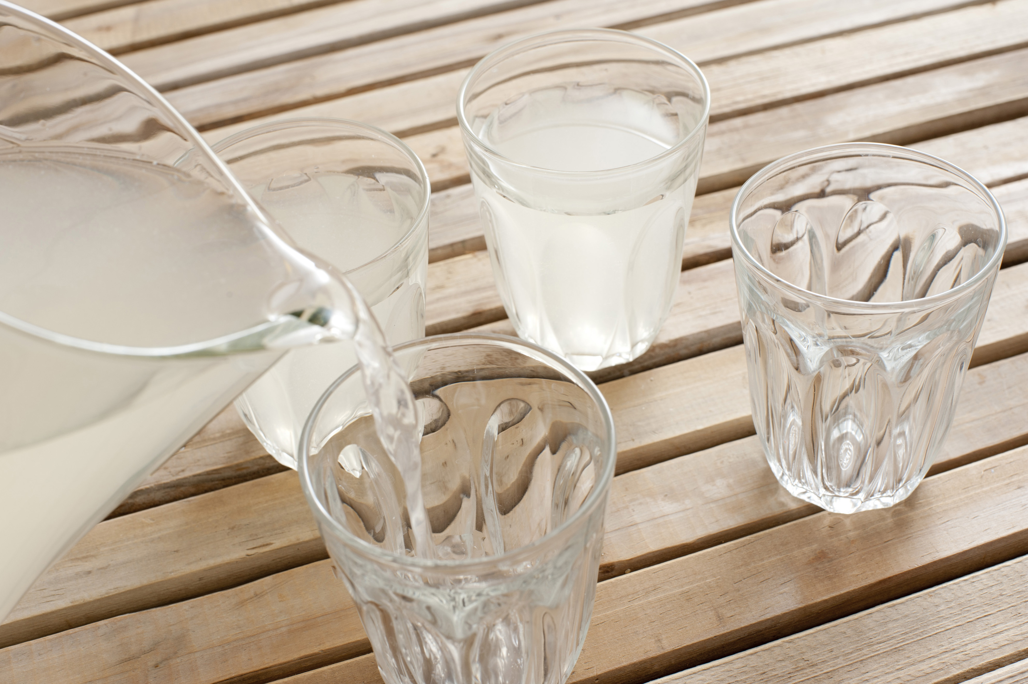 Pouring glasses of fresh homemade lemonade from a jug outdoors on a wooden garden table, closeup of the spout of the jug and pouring liquid