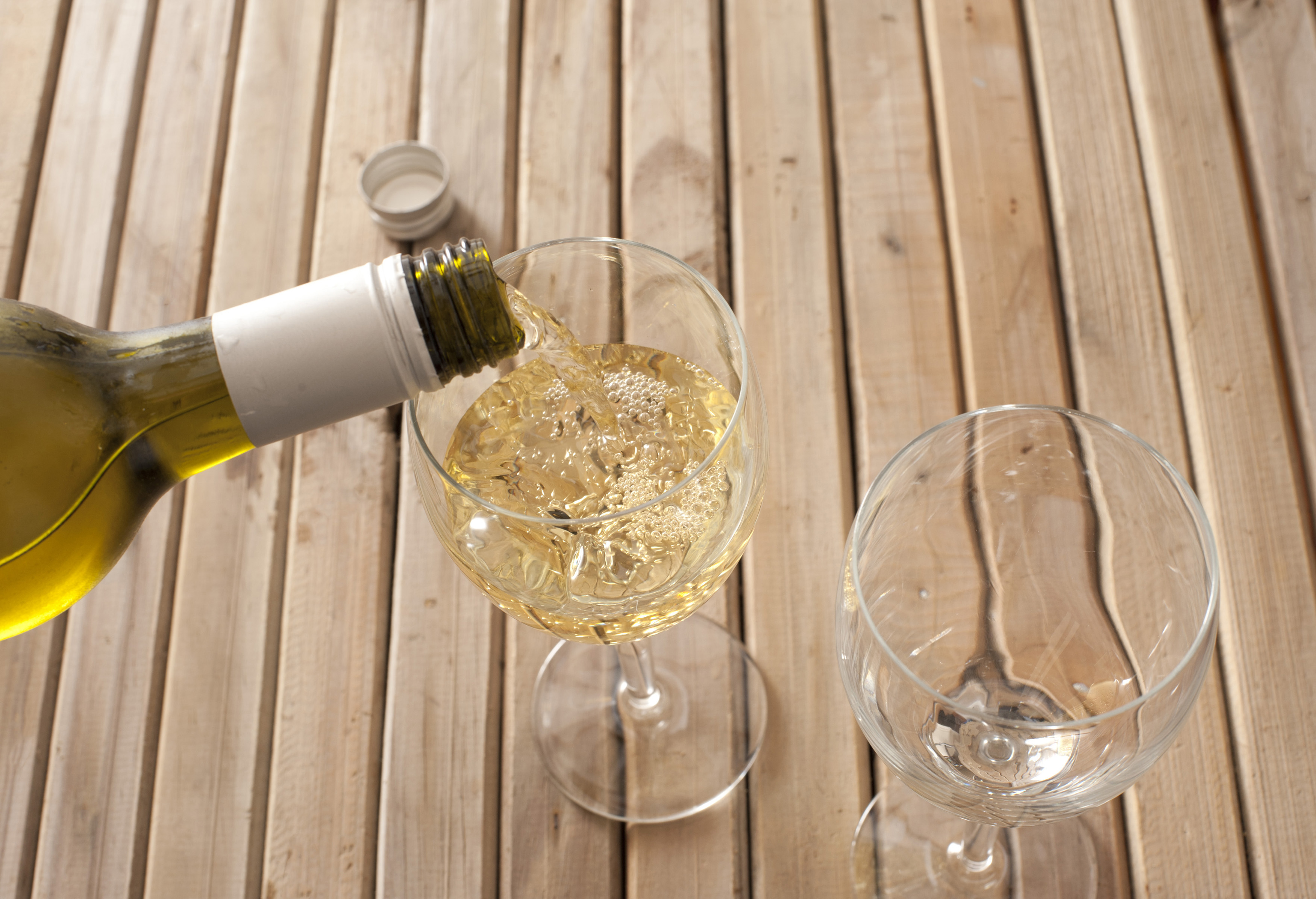 Pouring a glass of white wine from a bottle into a wineglass standing on a slatted wooden table, close up high angle view of the neck of the bottle and glass, with copyspace