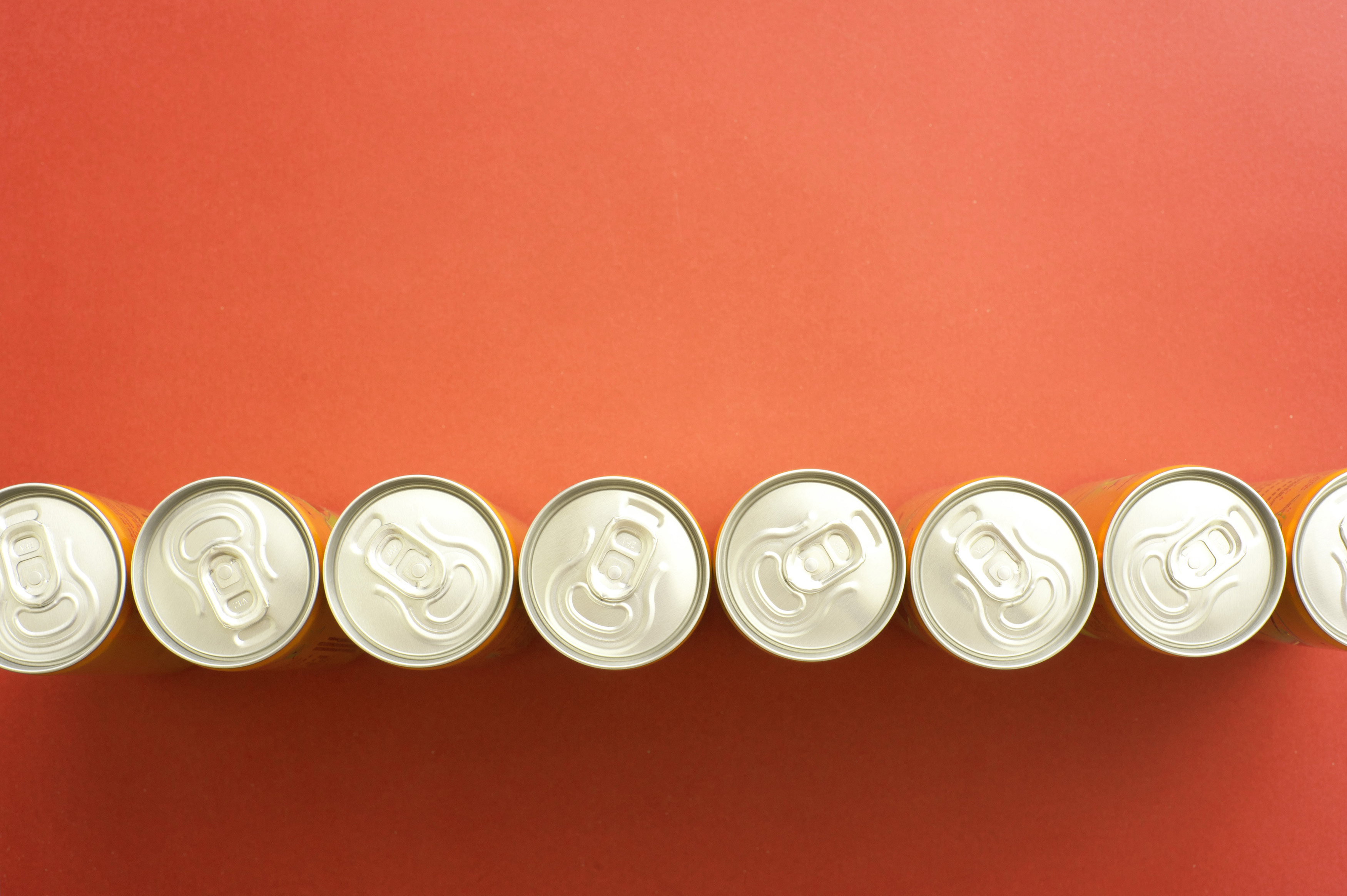 High Angle Still Life of Tops of Soda or Beer Cans Arranged in Line Across Orange Background with Copy Space - Generic Abstract Background