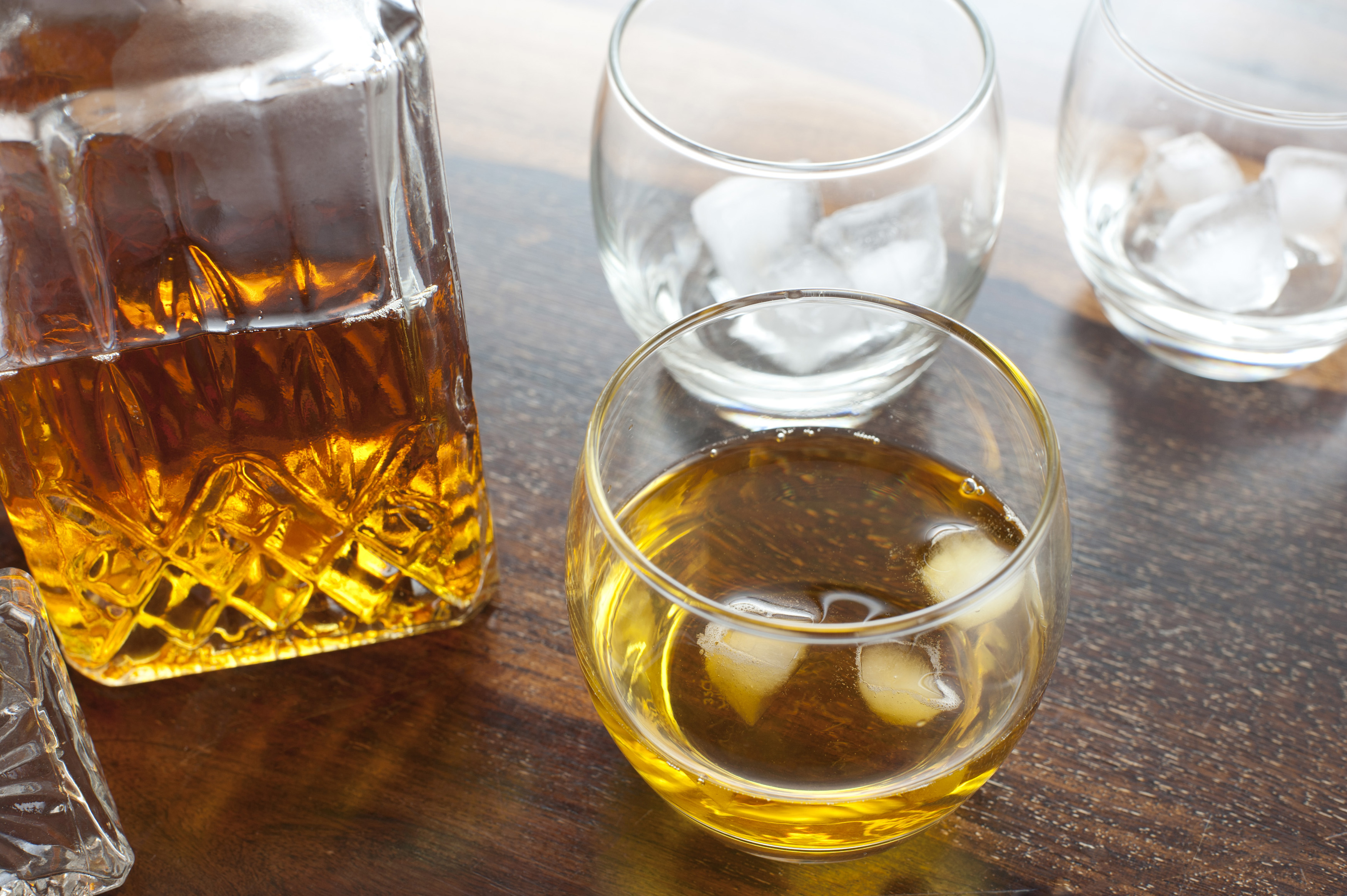 Scotch whiskey on the rocks served in a round tumbler with ice cubes alongside a cut glass decanter on a wooden table or bar counter
