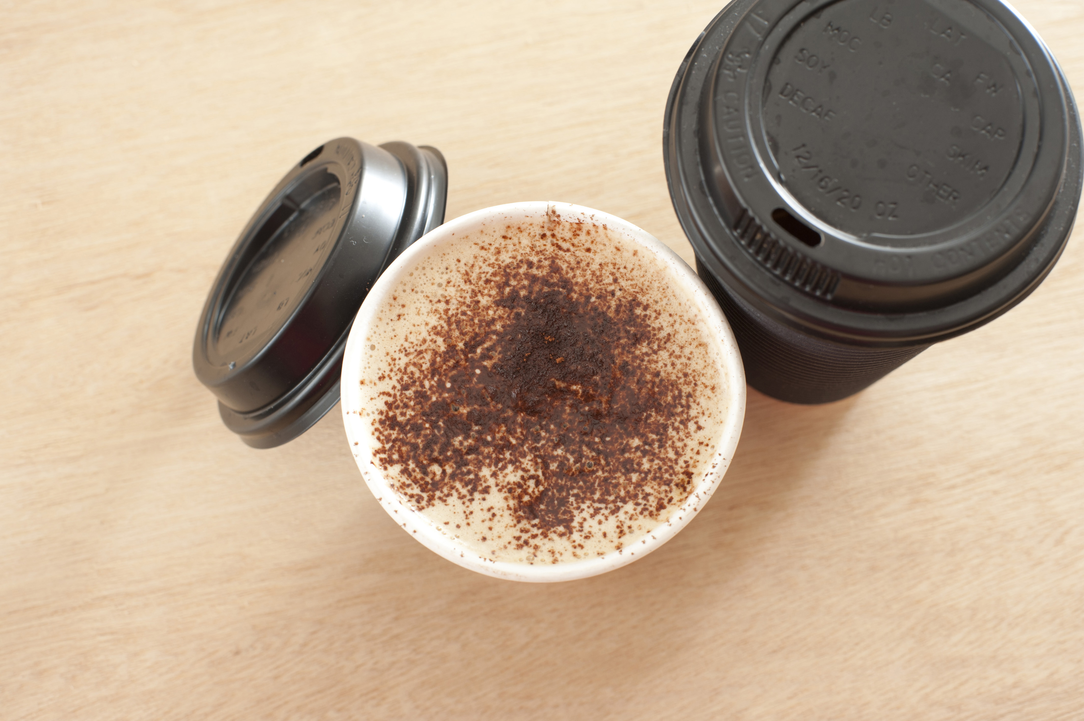 Two cups of freshly made frothy takeaway coffee in a disposable cup, one with the lid removed to reveal the beverage, on sealed, view from above
