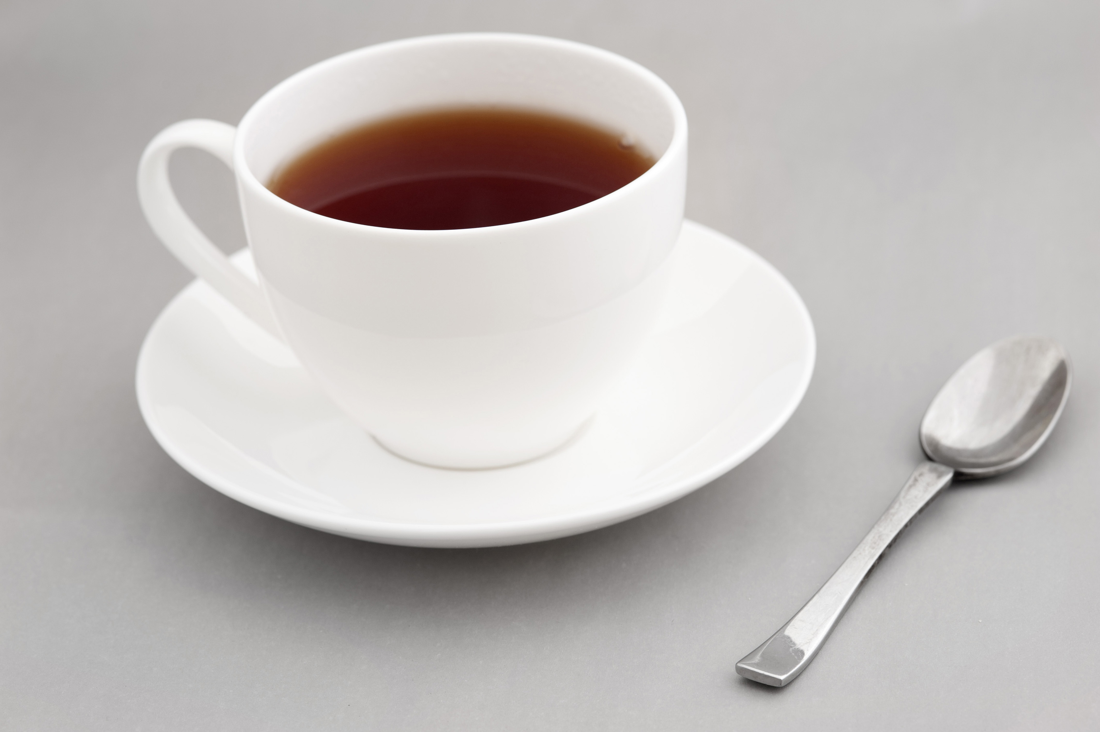 Generic white cup and saucer of hot black tea with a teaspoon alongside over gray