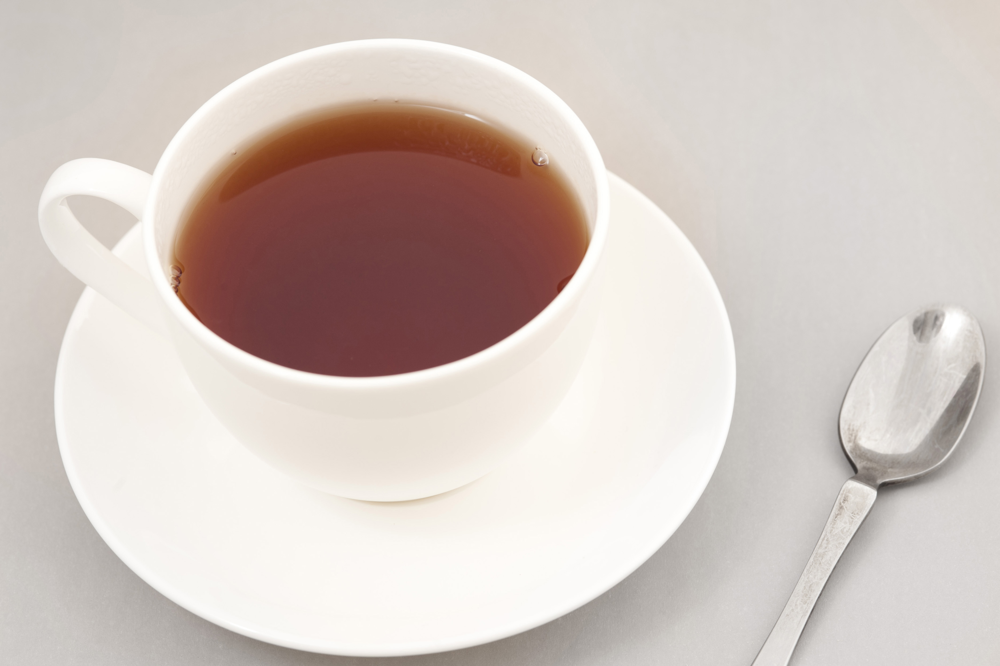 Cup of freshly brewed black tea in a generic white ceramic cup and saucer with a teaspoon alongside, high angle view