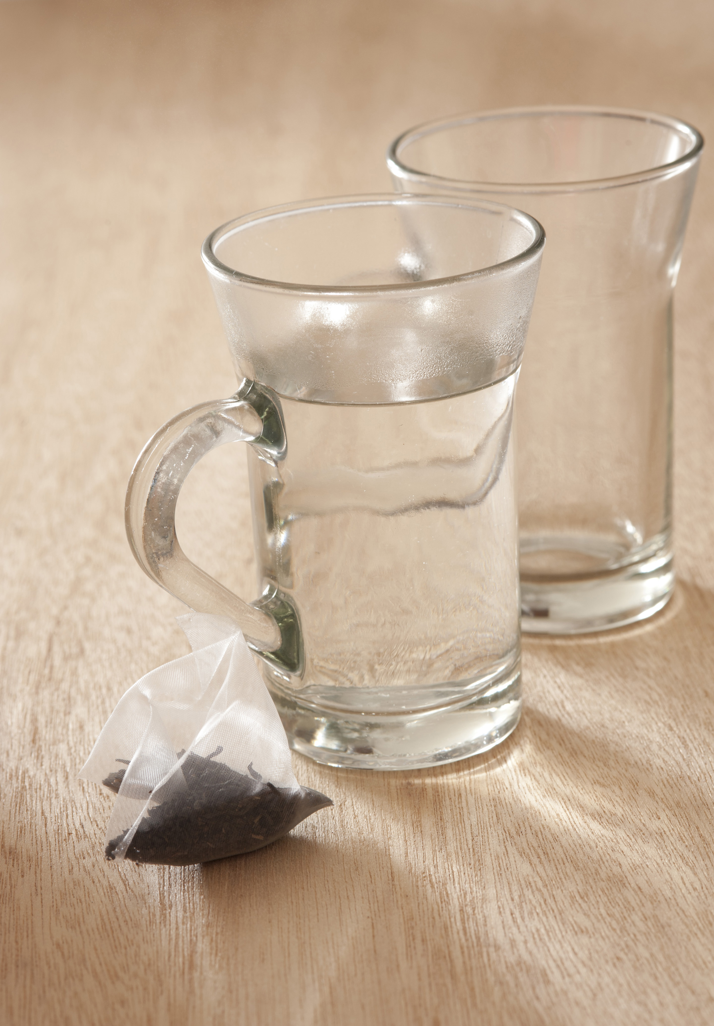 Glass mug filled with boiling water with a dry teabag standing ready alongside to prepare a fresh cup of aromatic relaxing tea