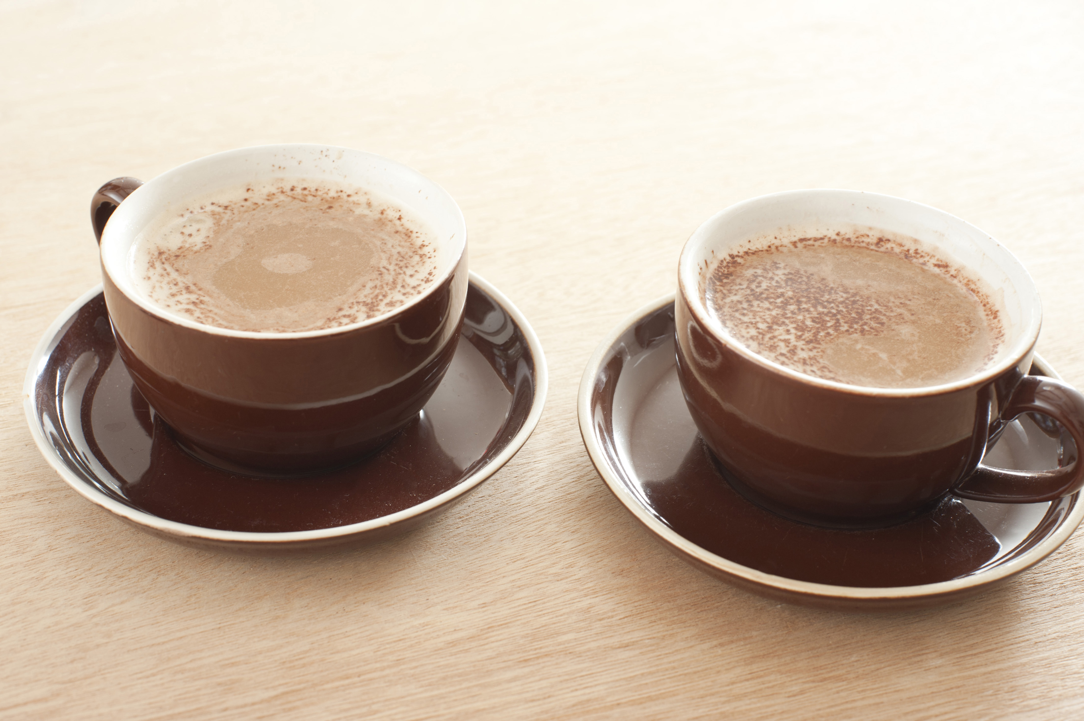 Two brown ceramic cups and saucers of fresh cappuccino coffee with a rich milky foam served on a wooden table with gradient color to white