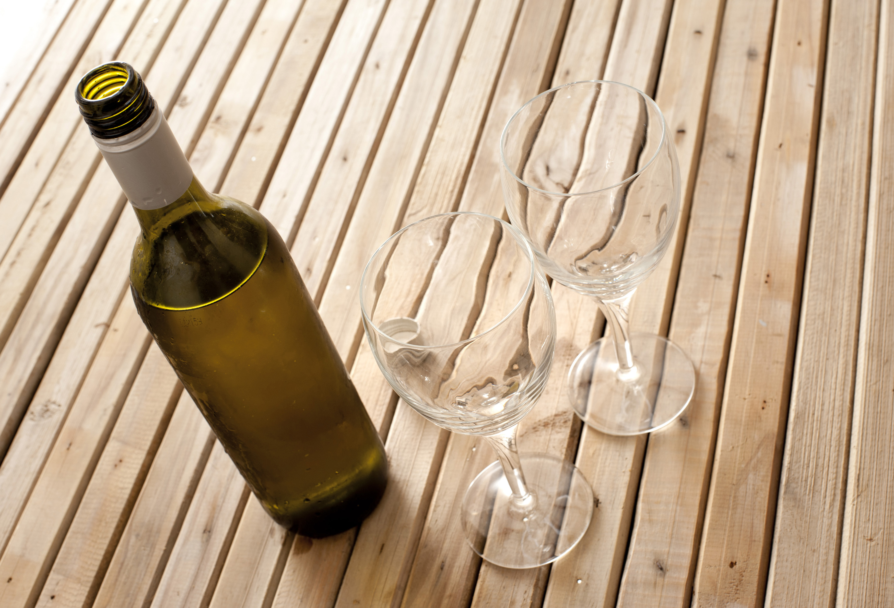 Bottle of opened white wine with two empty wine glasses viewed high angle on a wooden table conceptual of a celebration or entertaining