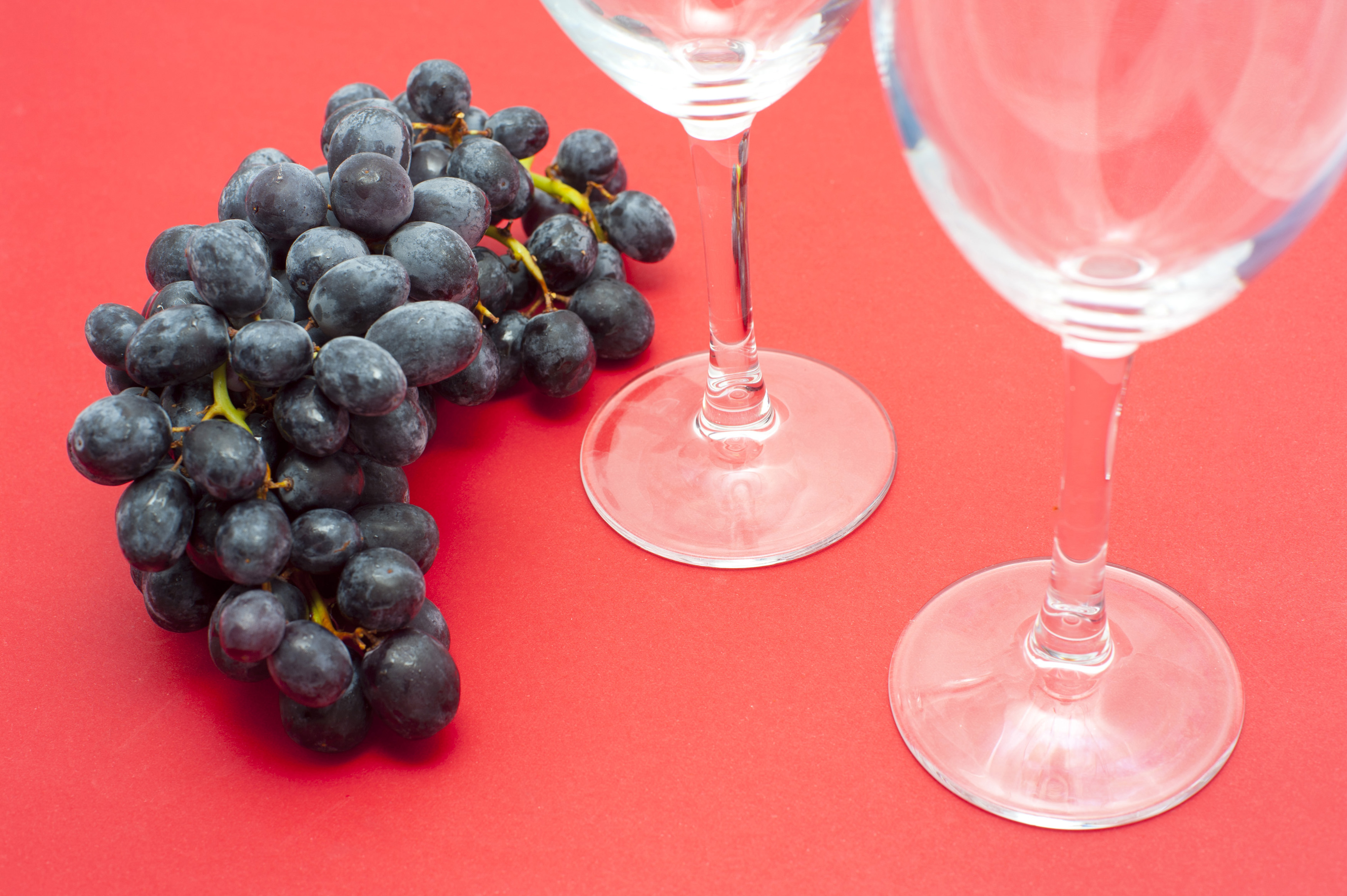 High Angle View of Red Wine Grapes and Two Empty Wine Glasses on Red Background with Copy Space