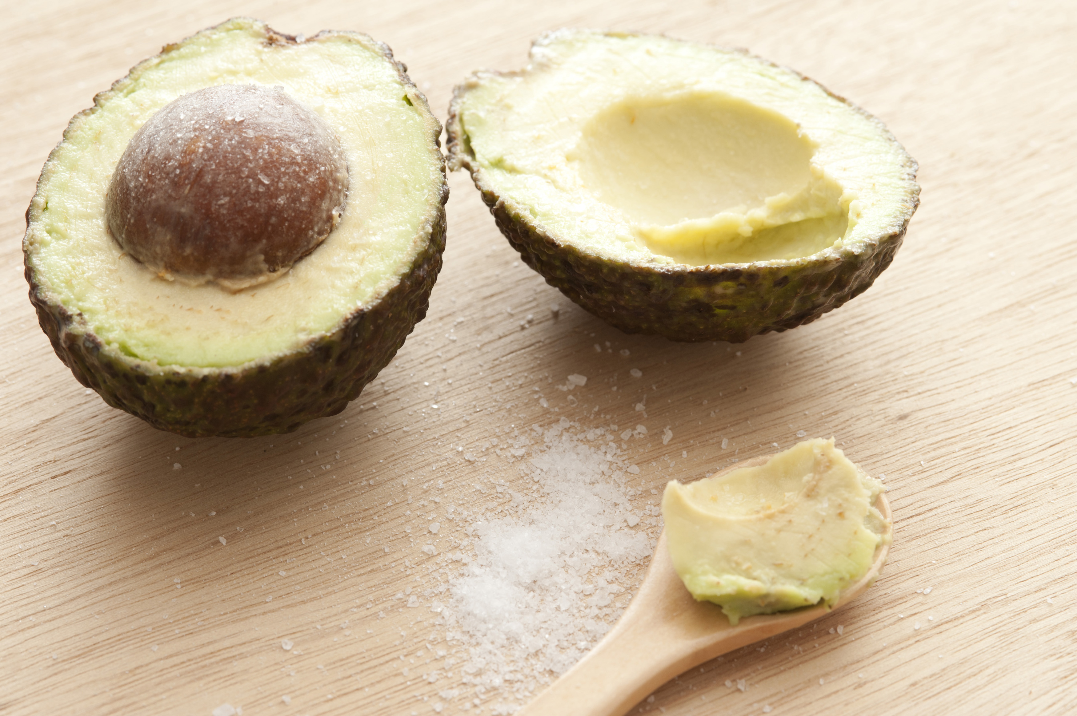 Delicious halves of avocado with salt and spoon on wooden table