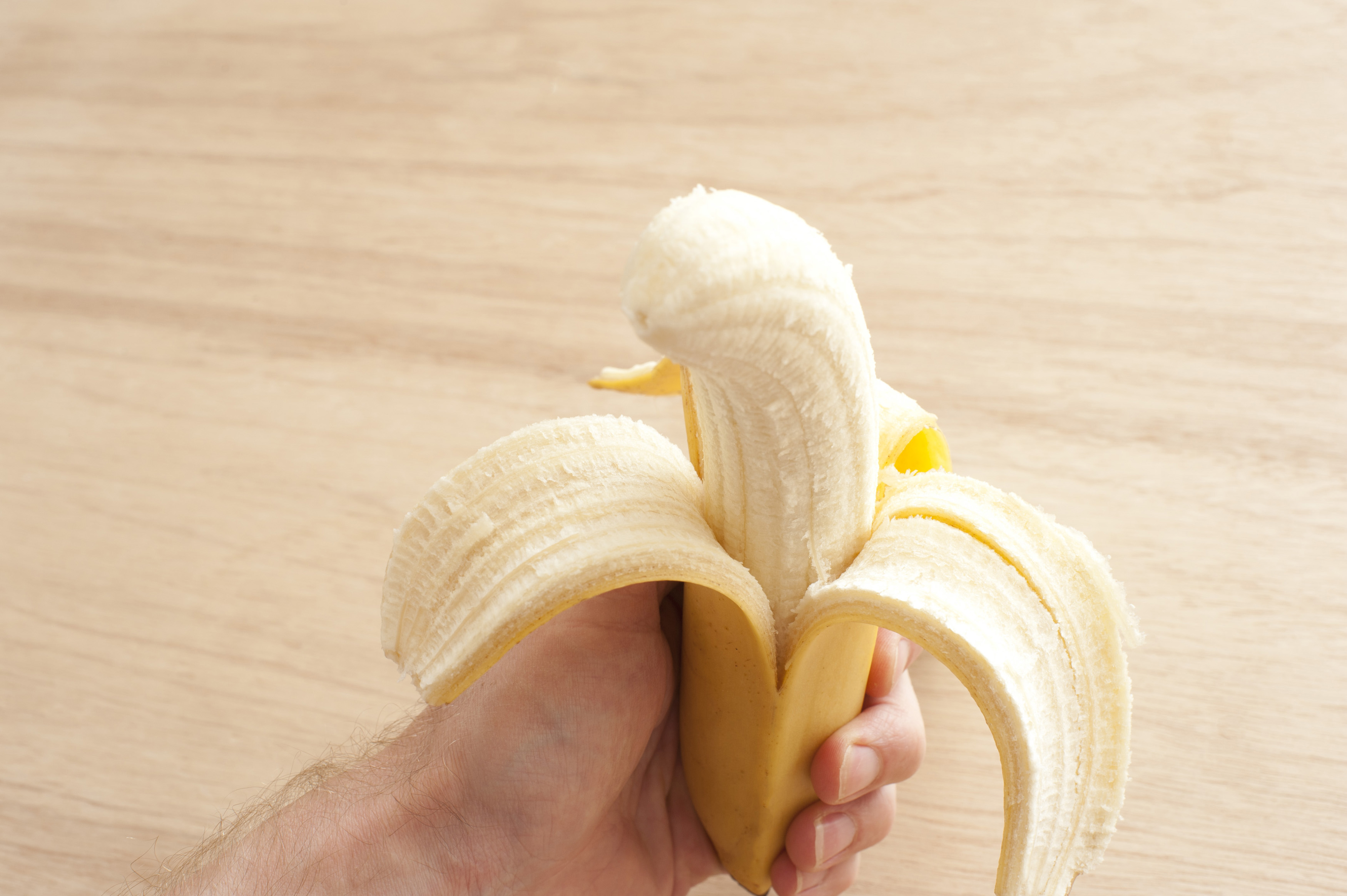 Uncorked banana in man's hand against of wooden background