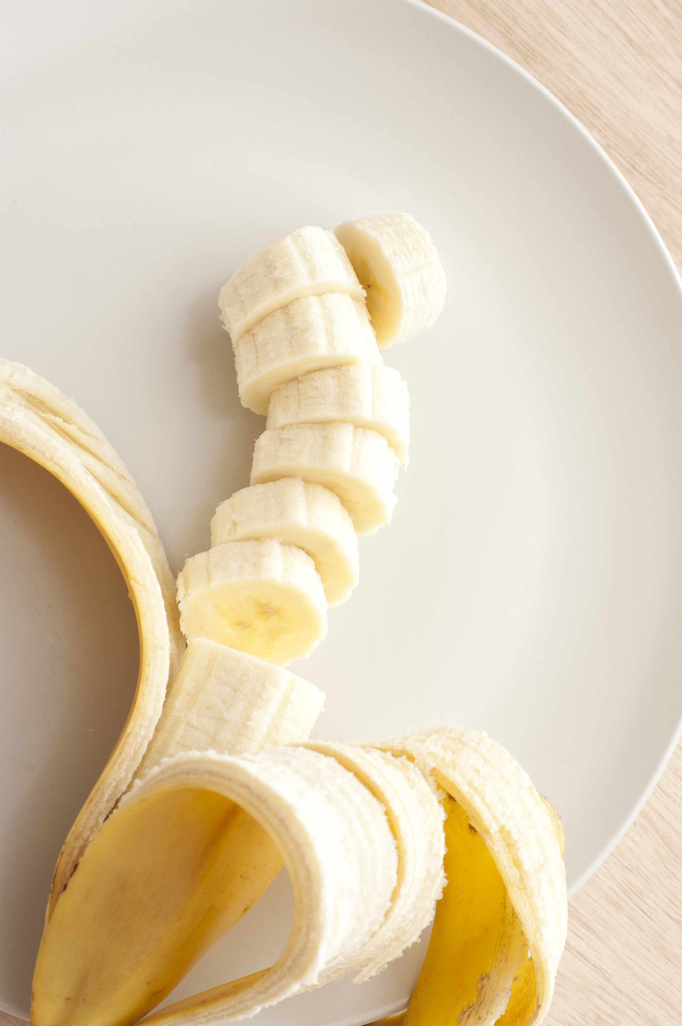 High Angle Close Up Still Life of Ripe Banana Partially Peeled and Sliced on White Dinner Plate with Copy Space