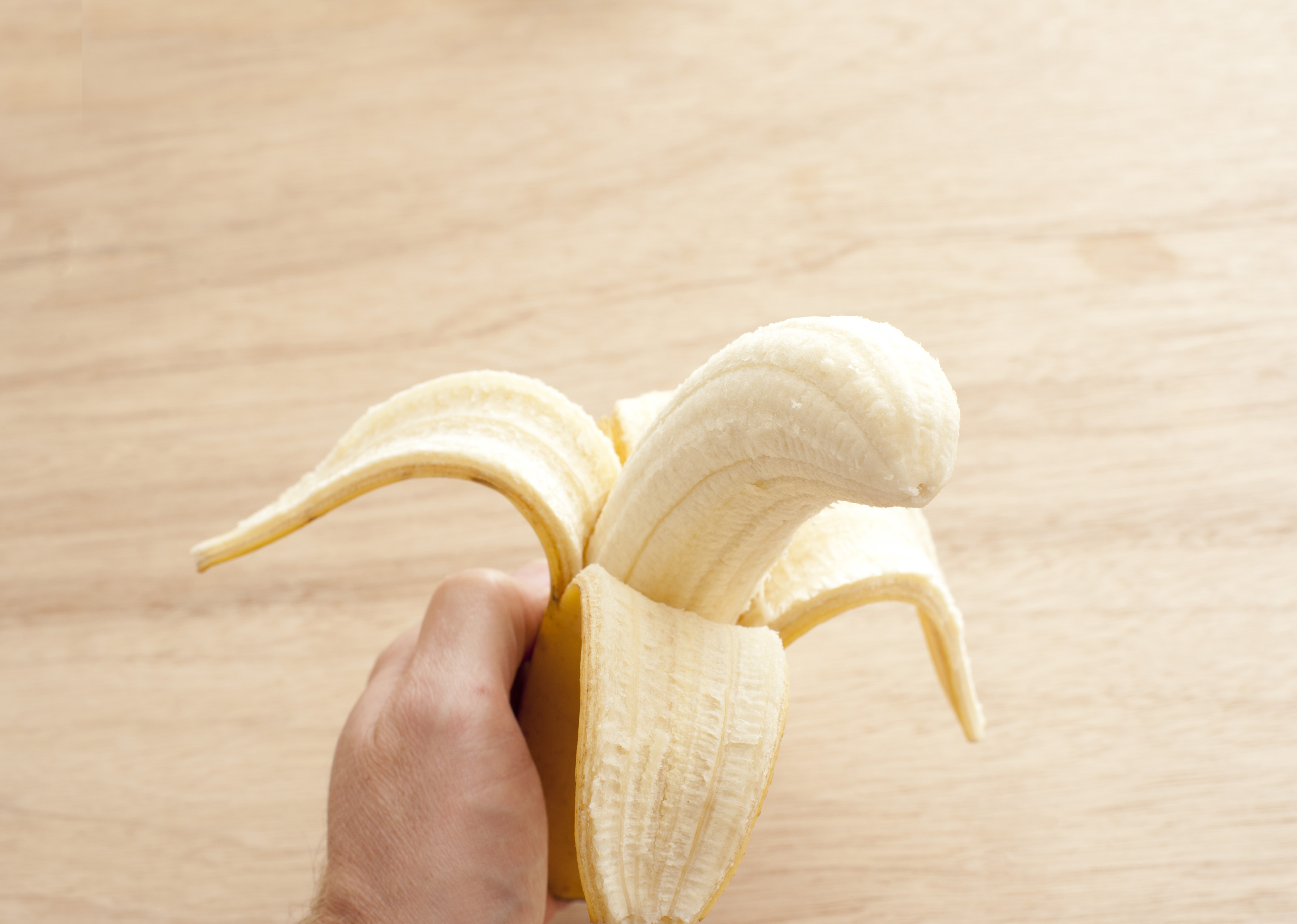 Man eating a ripe fresh banana holding it in his hand with half the skin peeled back to reveal the fruit, over a wooden background