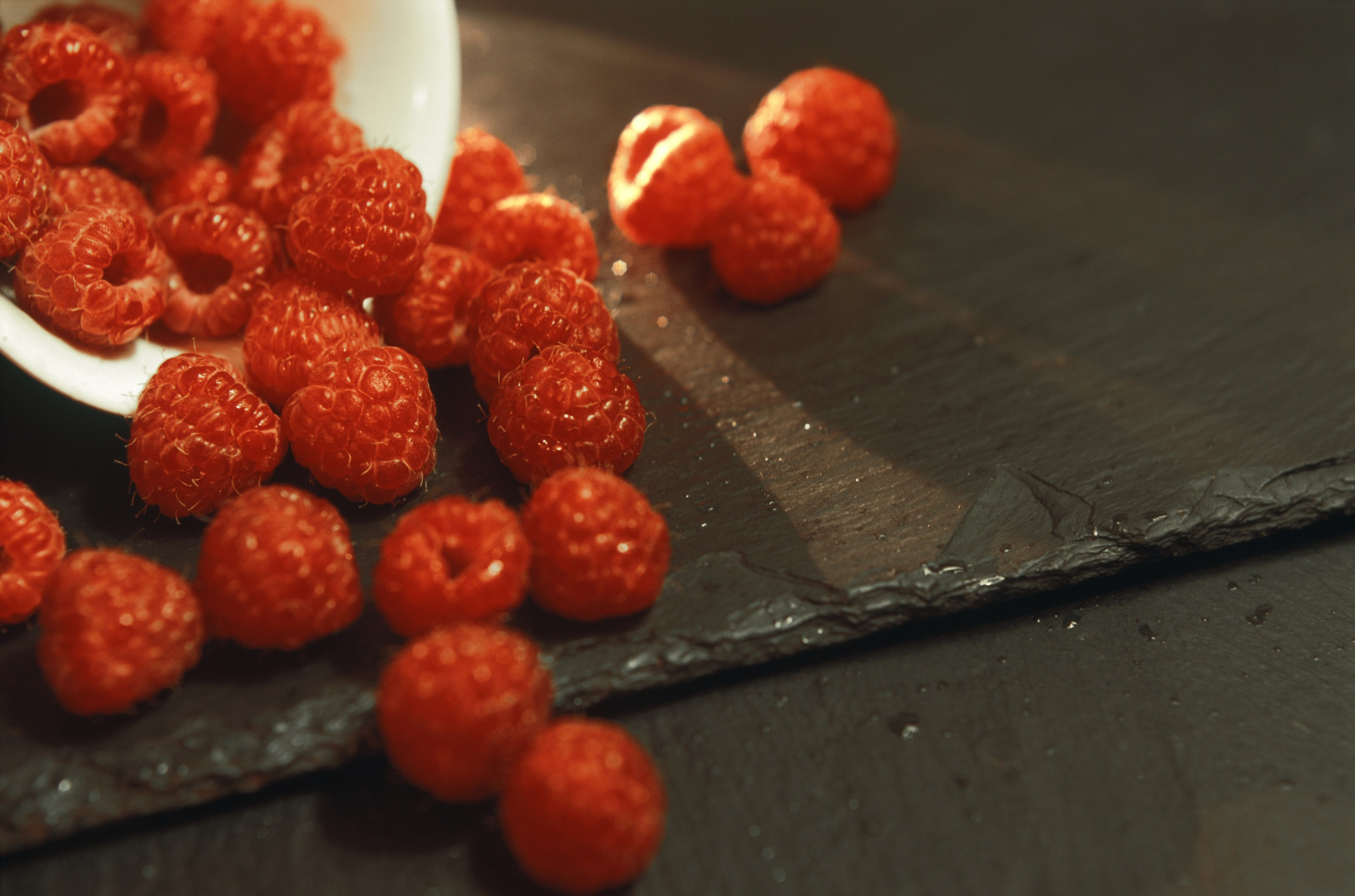 Ripe red autumn raspberries spilling out of a ceramic dish onto an old wooden tabletop, closeup view