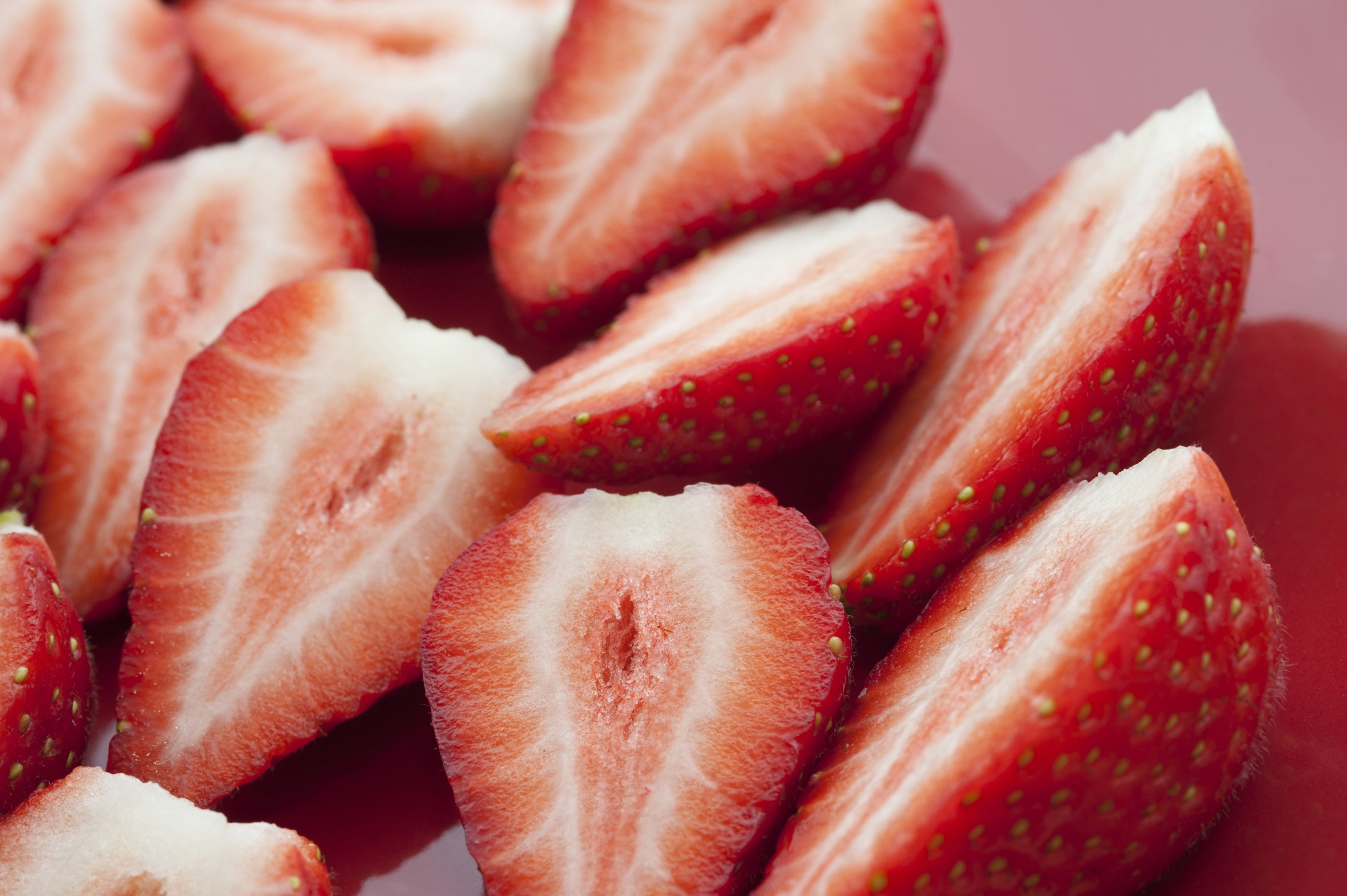 Close up view of halved strawberries showing the succulent sweet flesh during preparation of a delicious dessert