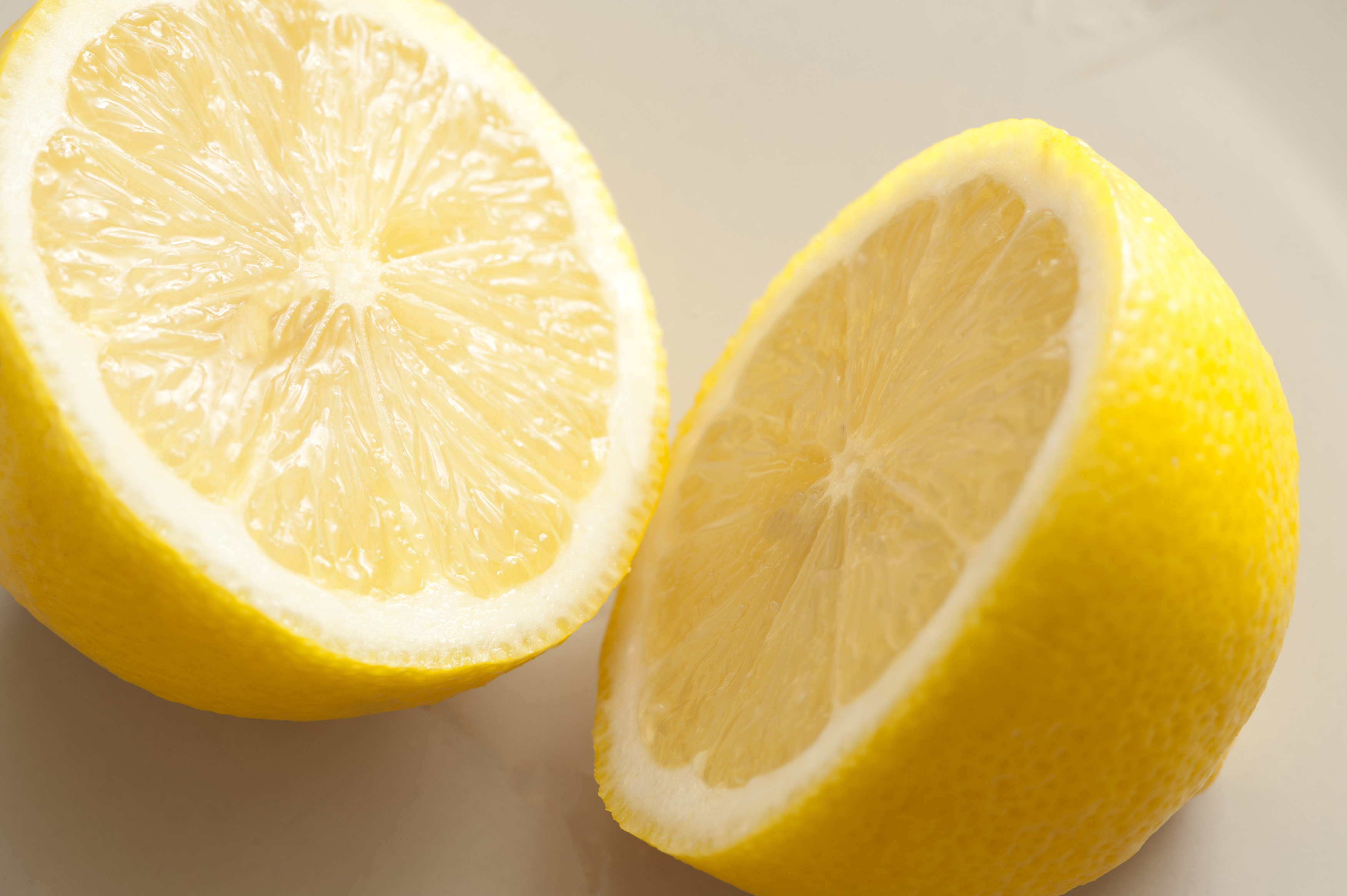 A lemon sliced in two on a grey background