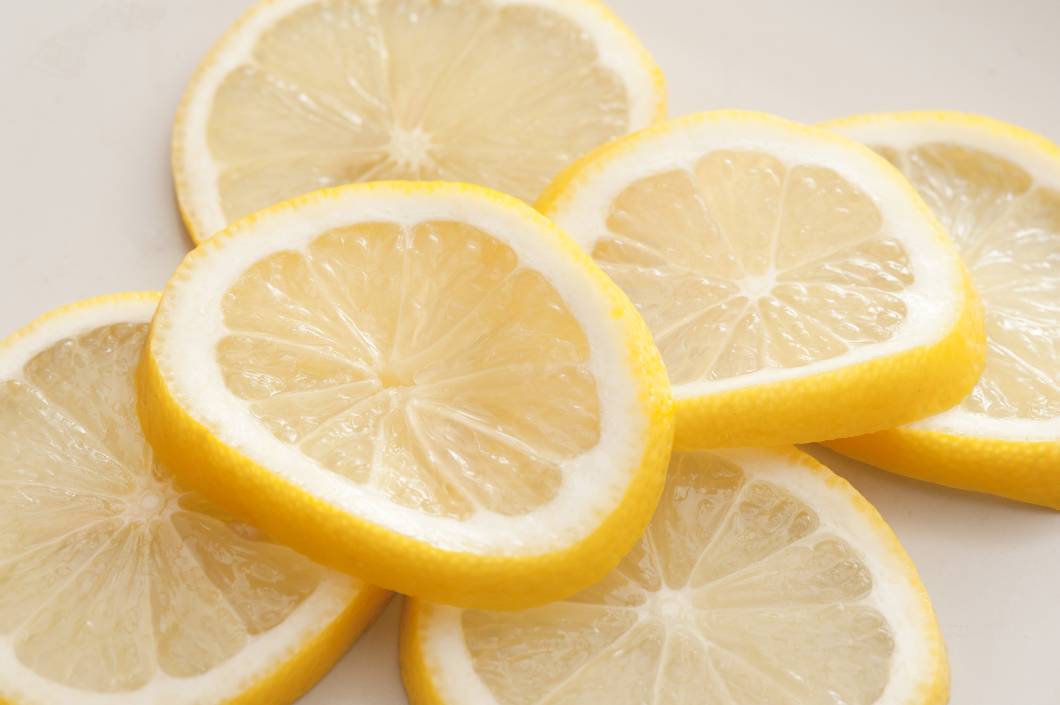 Heap of fresh ripe juicy lemon slices on white for use as a garnish in drinks and food, close up view