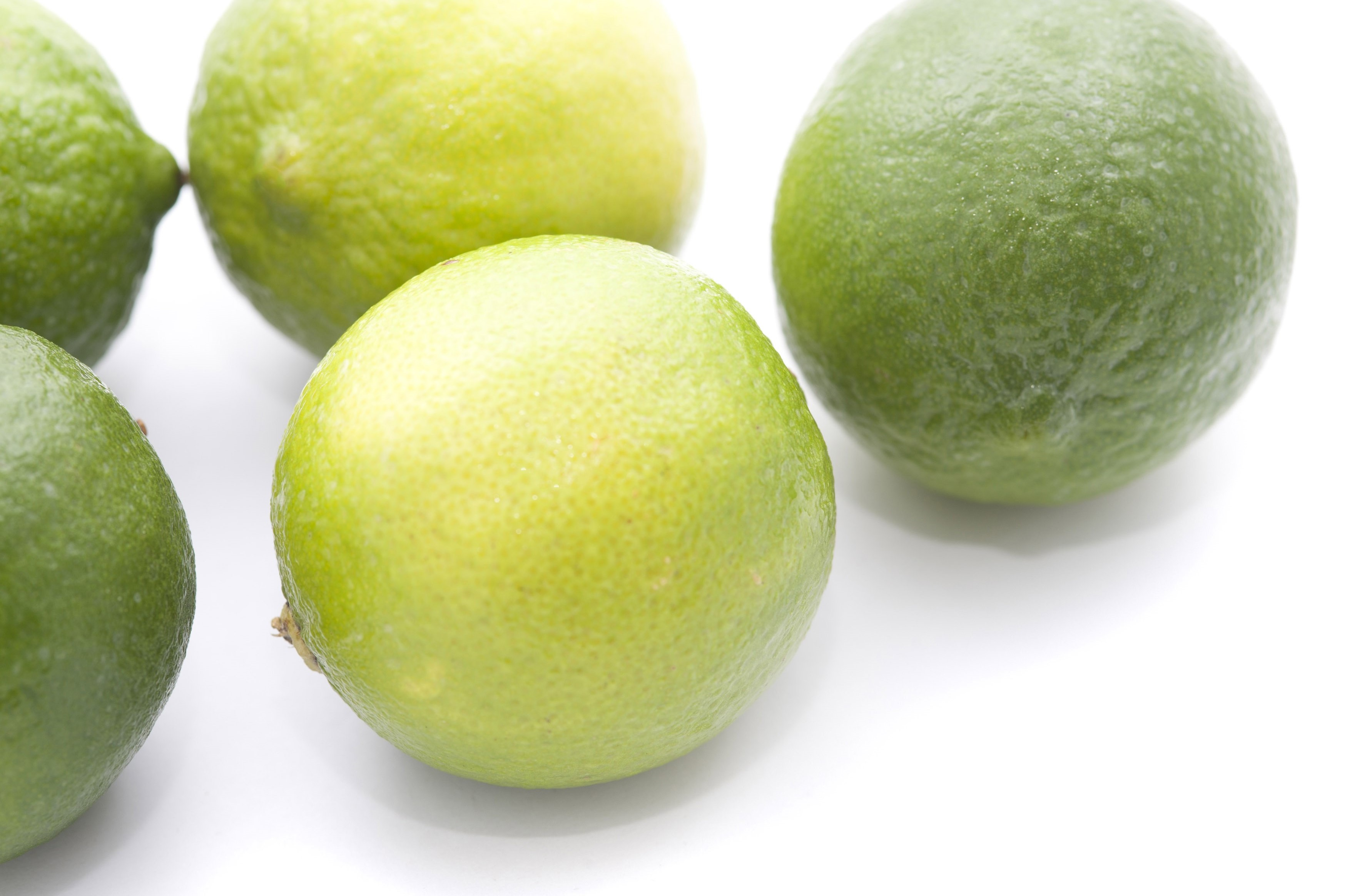 Fresh whole limes, an acidic citrus fruit with a tangy taste used as a flavouring in cooking and as a garnish