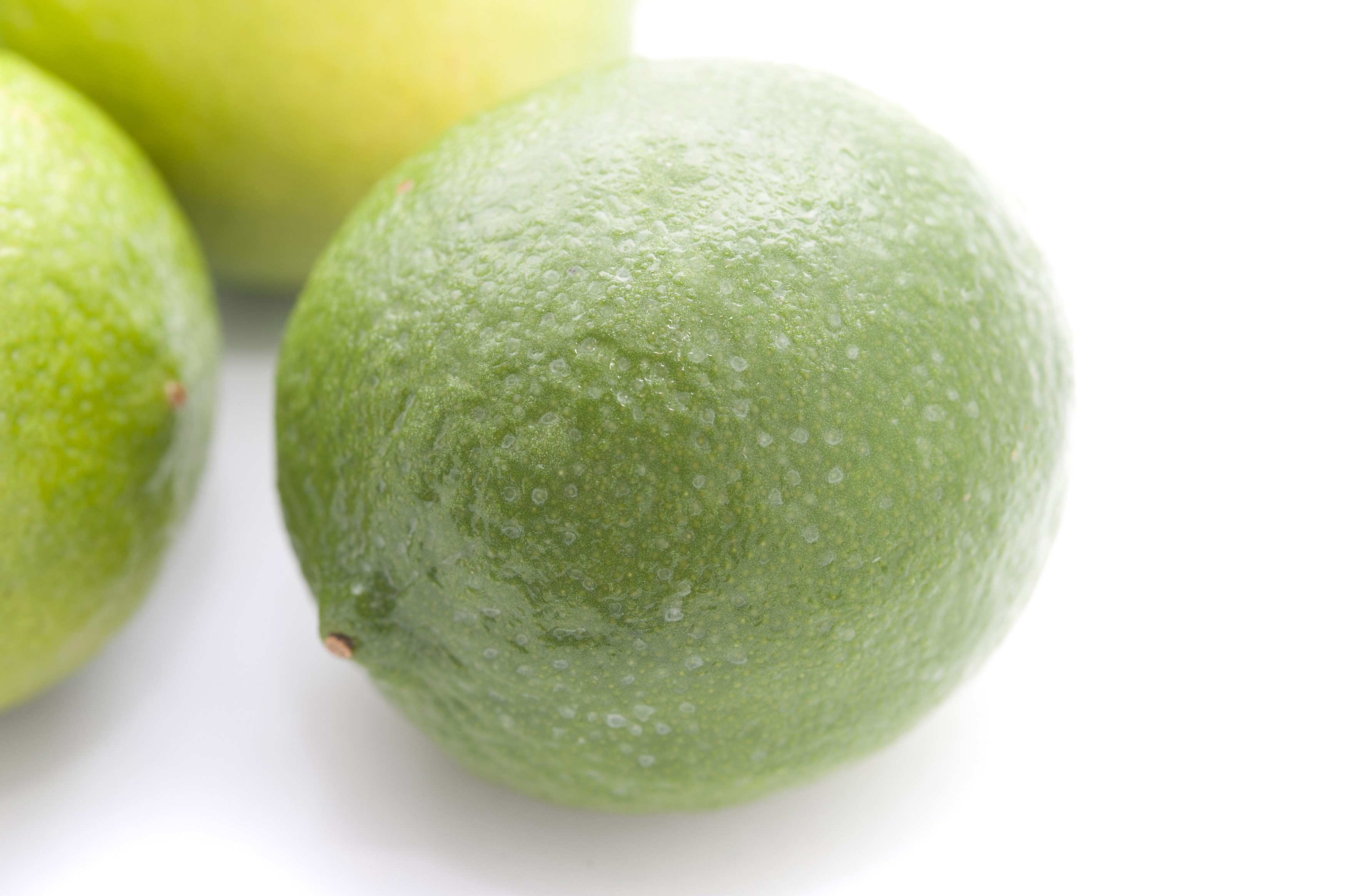Whole fresh green limes used in cooking for their tangy acidic taste as a flavouring and garnish, on a white background