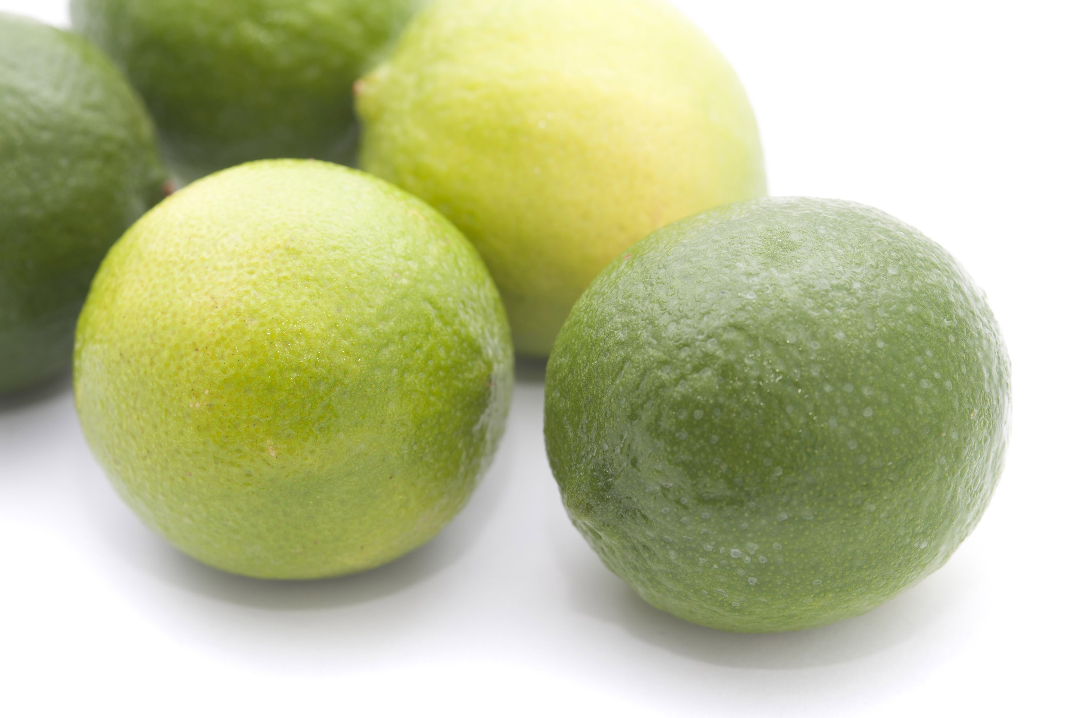 Nutritious fresh and green limes on white background, close-up