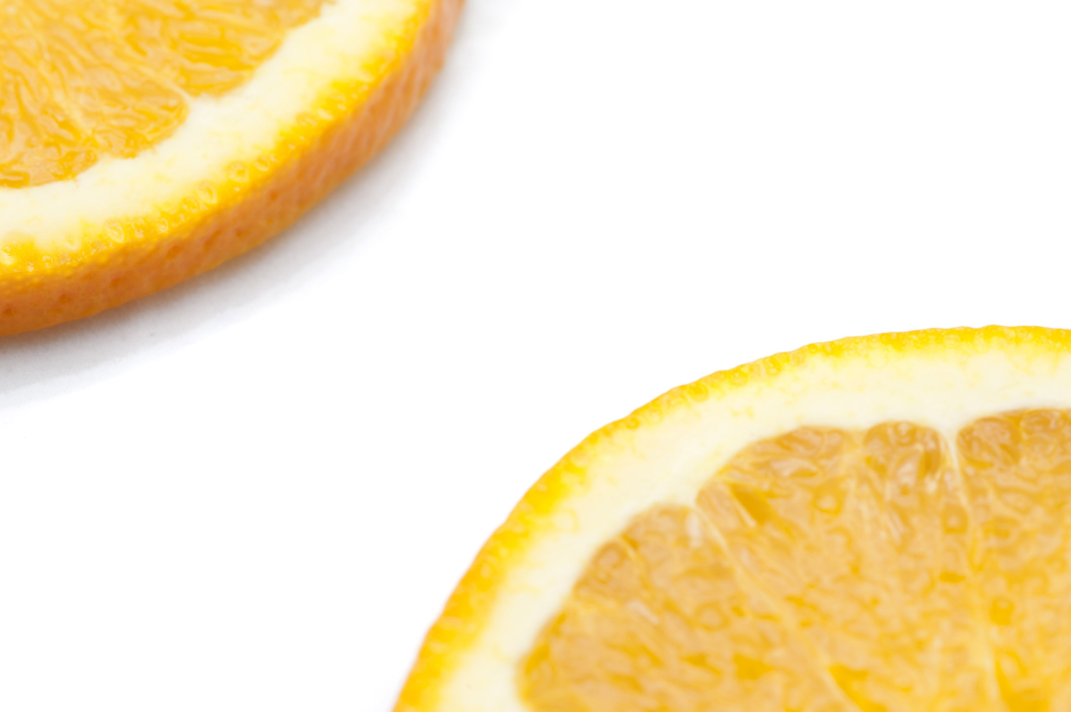 Partial view on a white background with copyspace between them of slices of fresh juicy orange citrus fruit showing the texture of the pulp