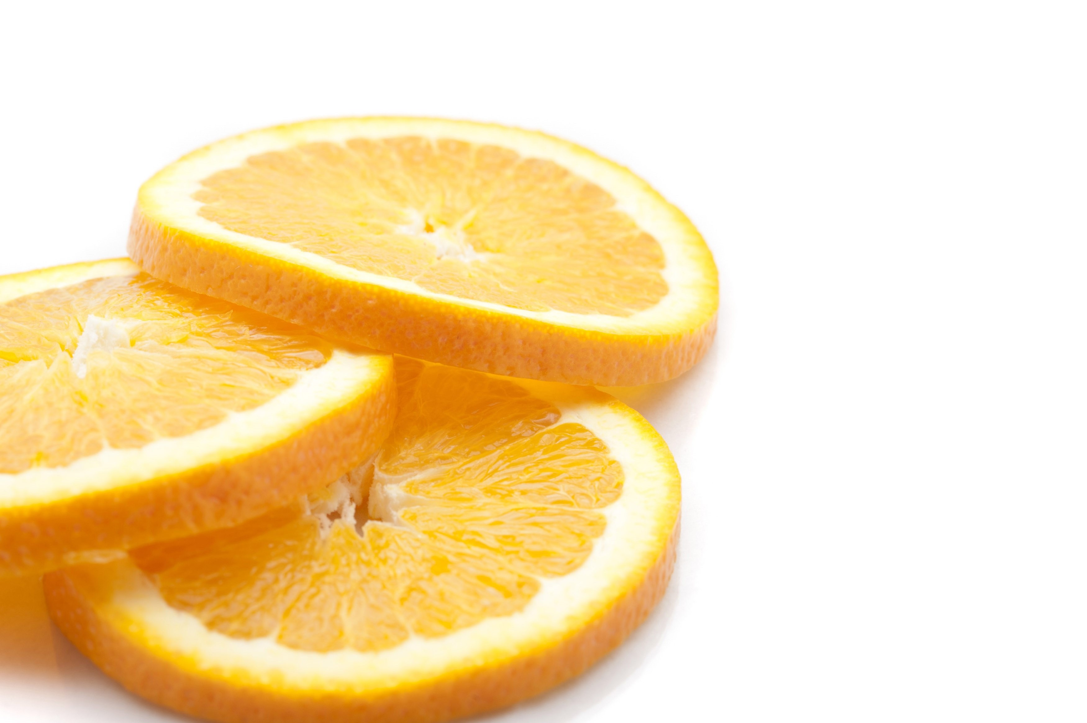 Closeup view of three slices of thinly sliced fresh orange showing the segmented pulp and rind ready for use as a garnish lying on a white background with copyspace