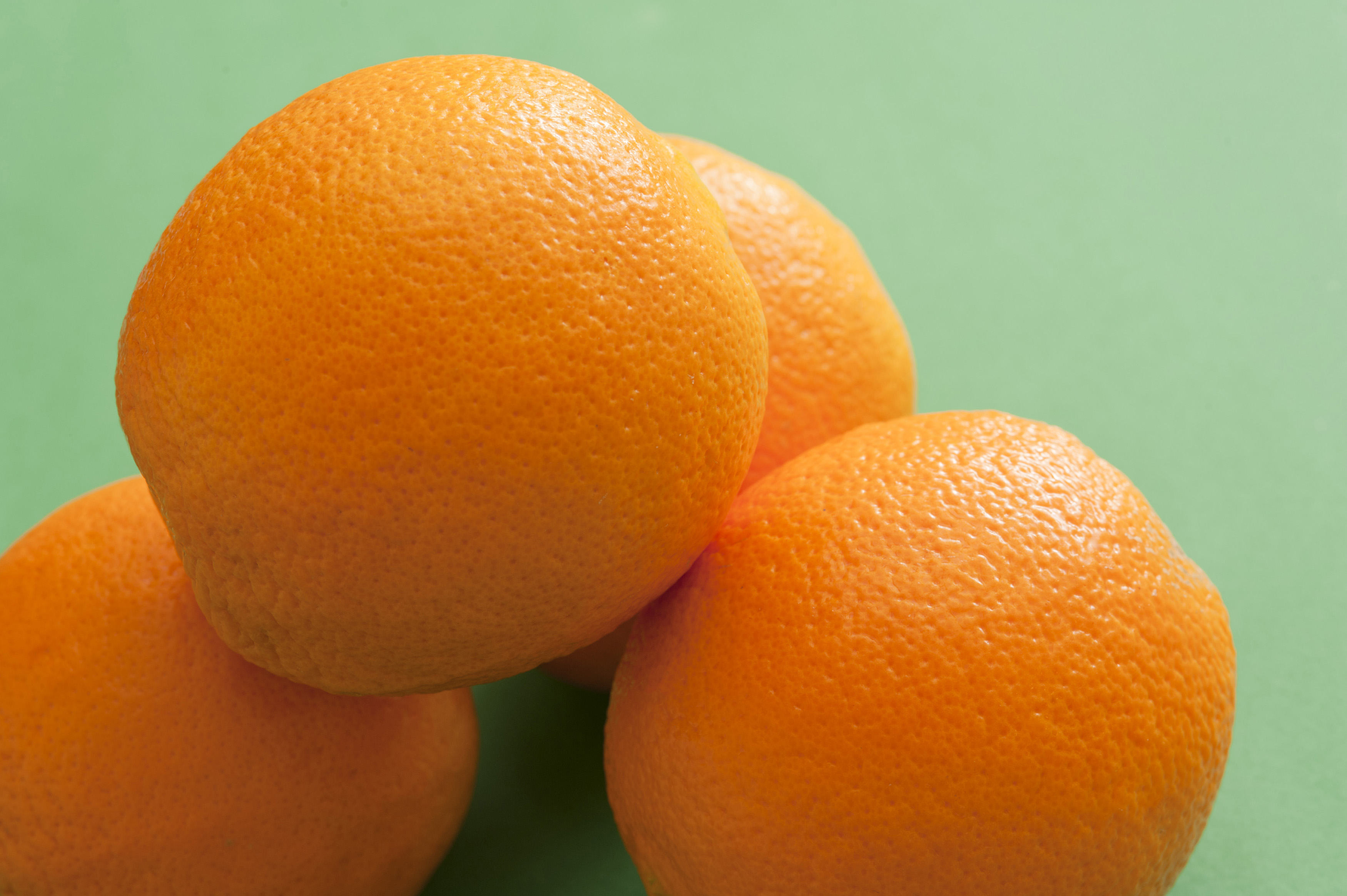Close-up of several oranges on green background