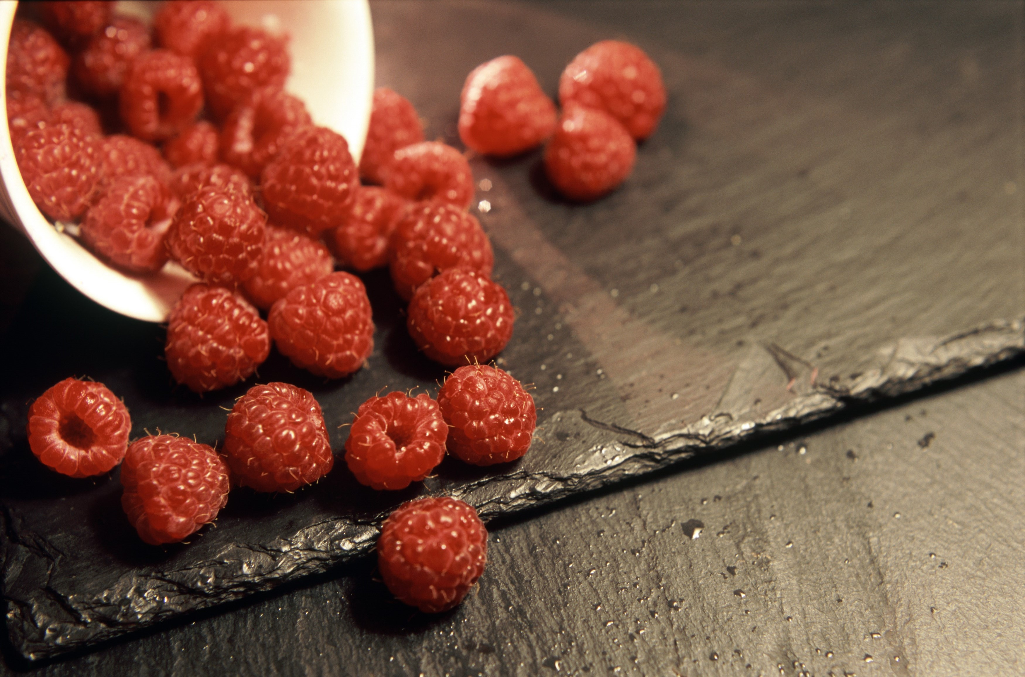 Delicious healthy ripe red raspberries spilling from a small ceramic container onto an old wooden surface with copyspace