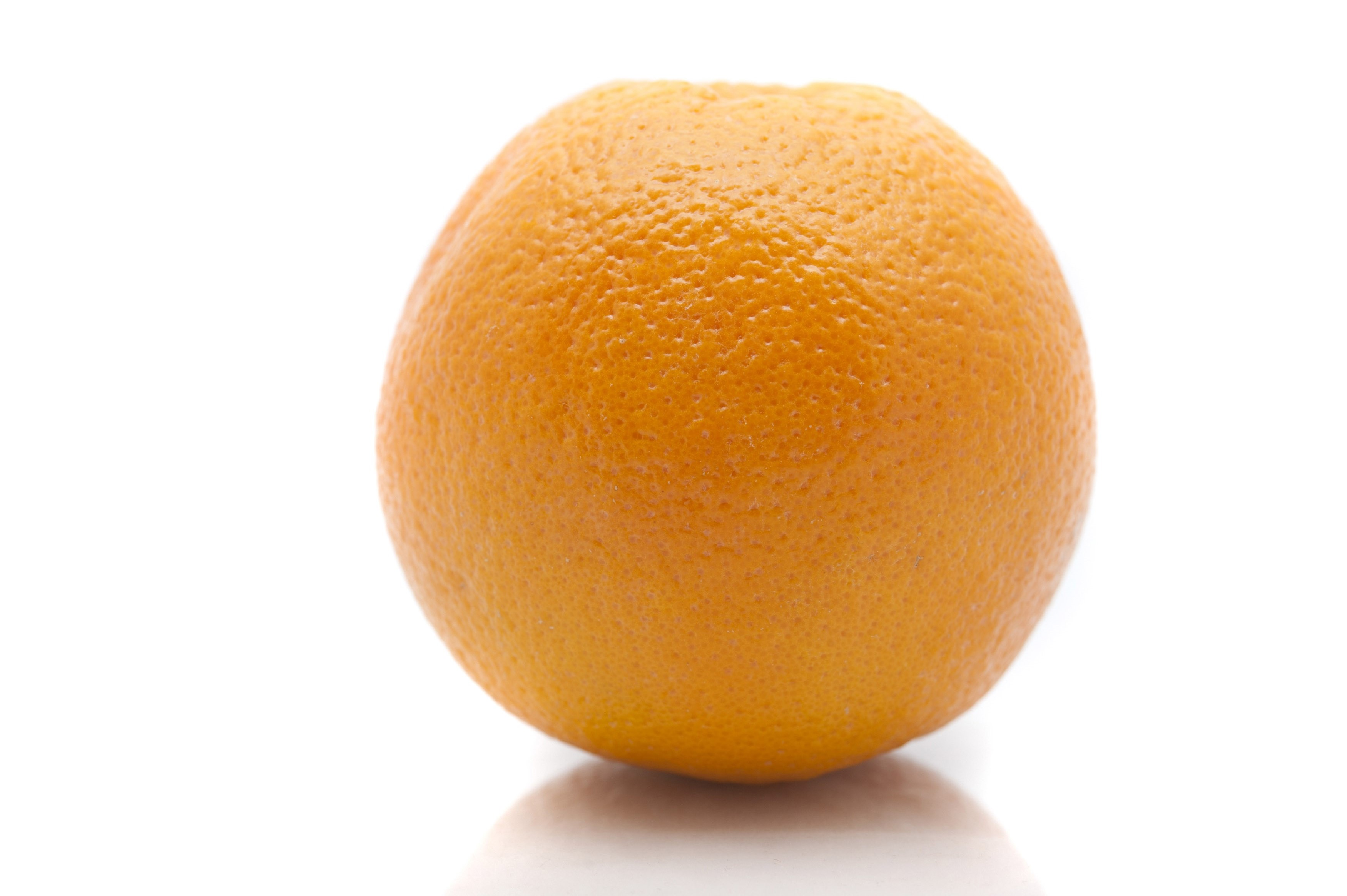 Close up view of one whole fresh orange showing the texture of the rind over a white background