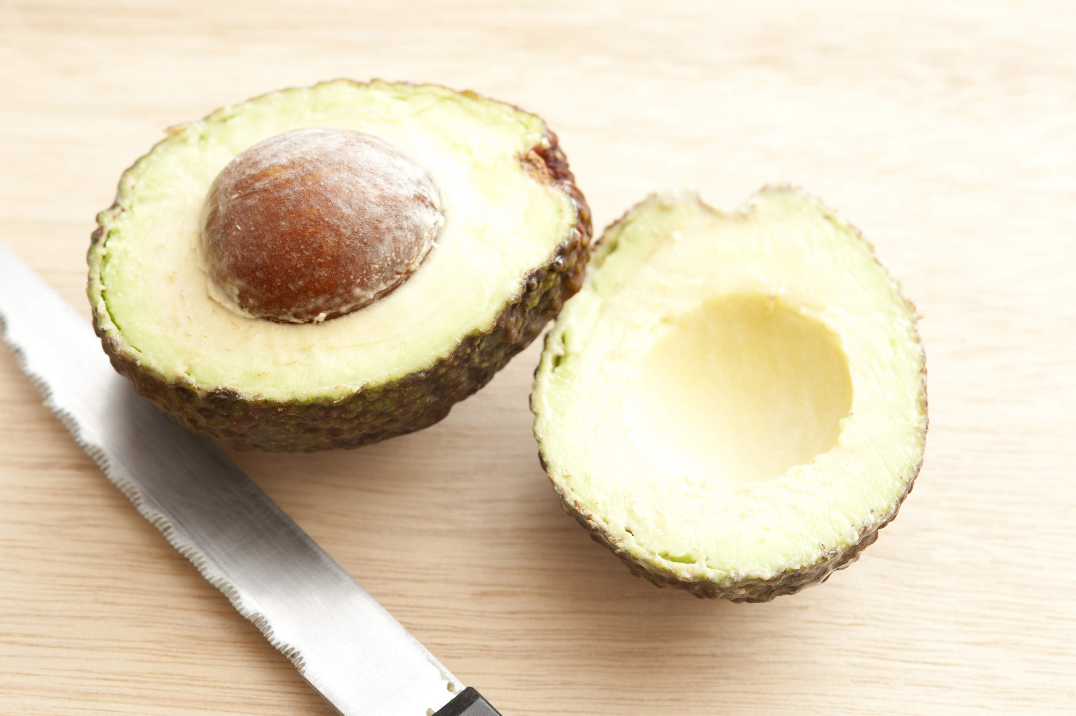 Fresh cut avocado with seed and knife on wooden table