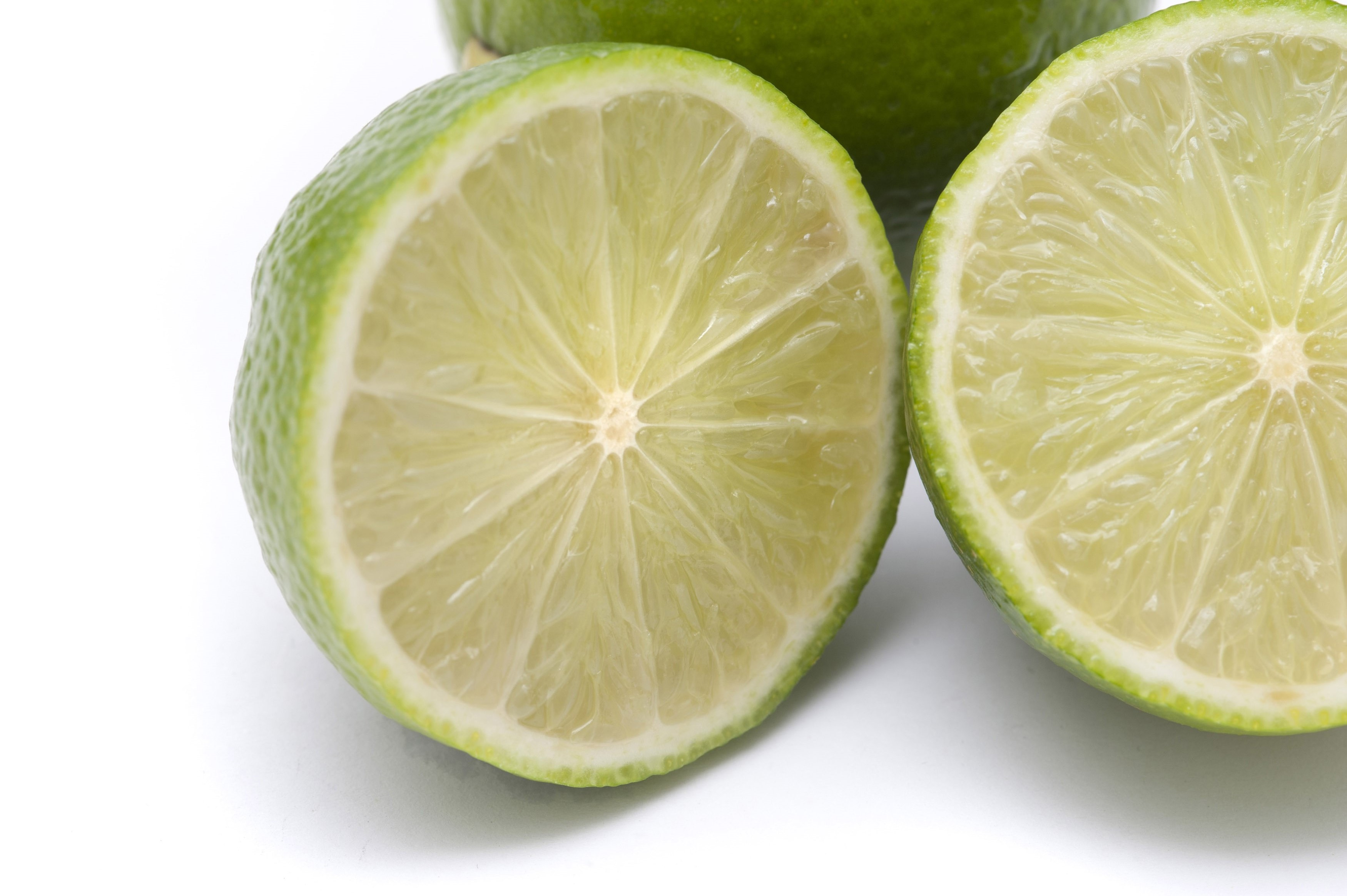 Closeup of a halved fresh lime showing the pulp texture and segments on a white background