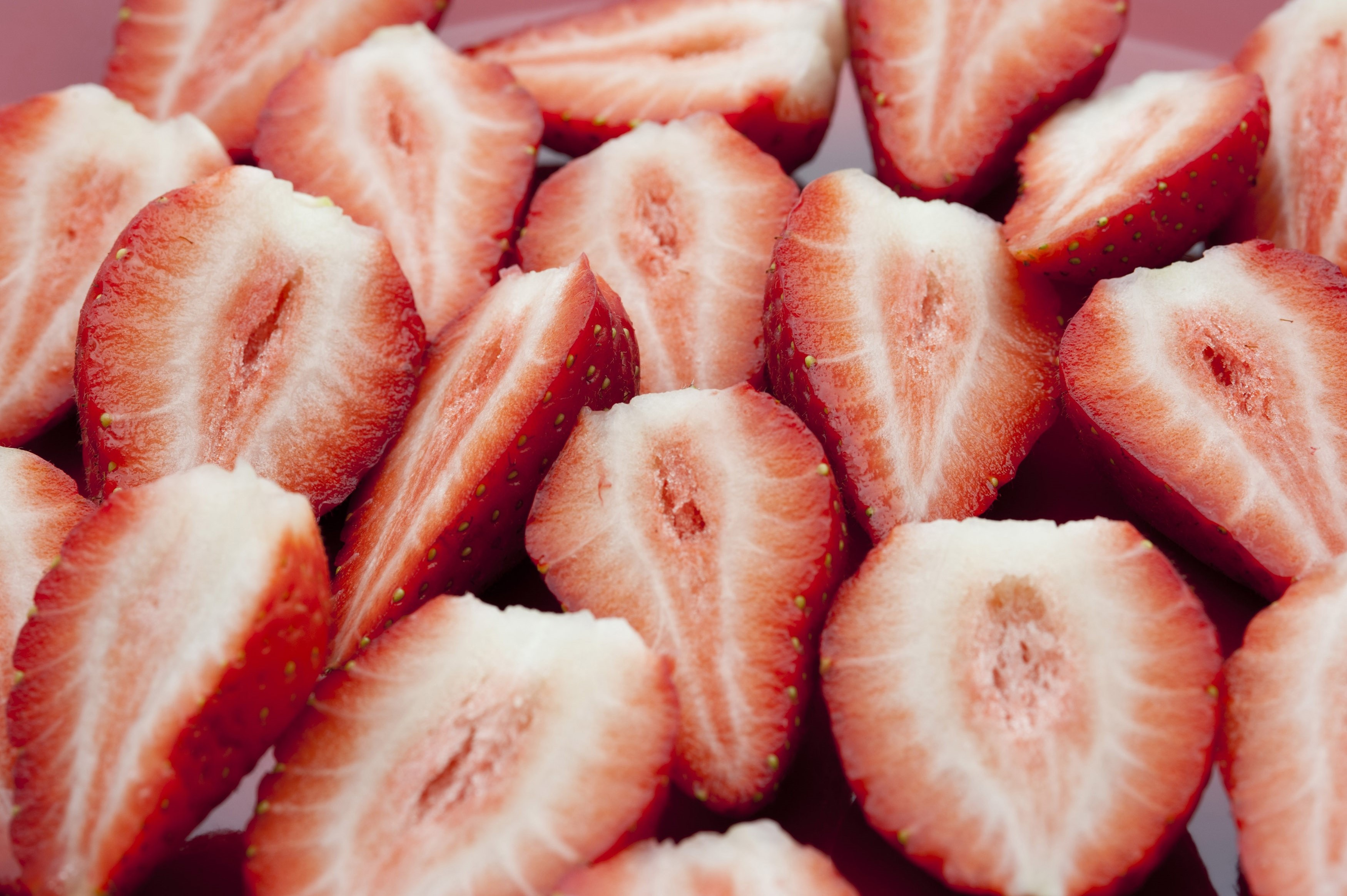 Background of sliced halved fresh strawberries showing the sweet tasty pulp prepared for a delicious dessert or ingredient in a meal