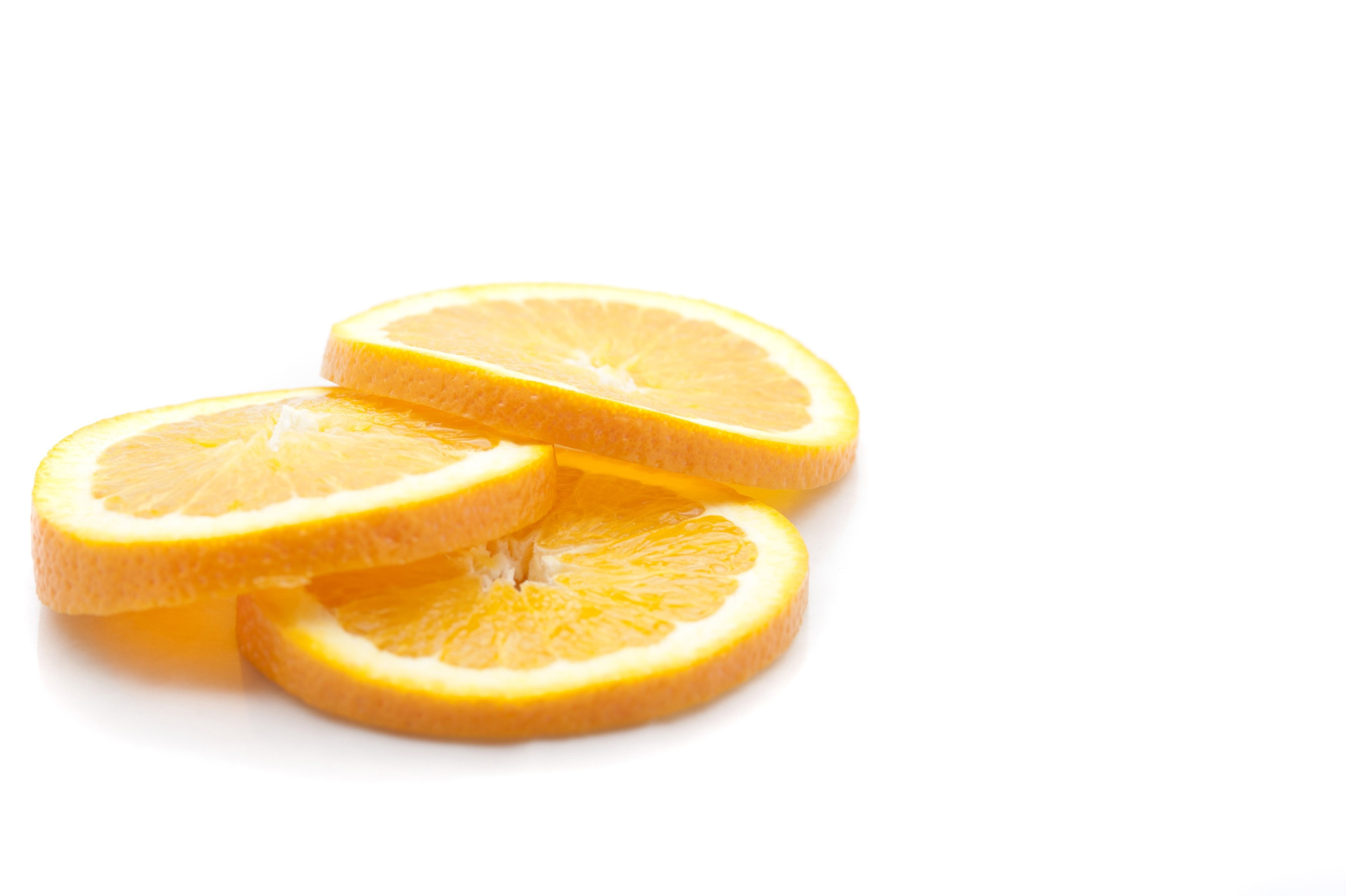 Three slices of fresh yellow juicy lemons, close-up on white background