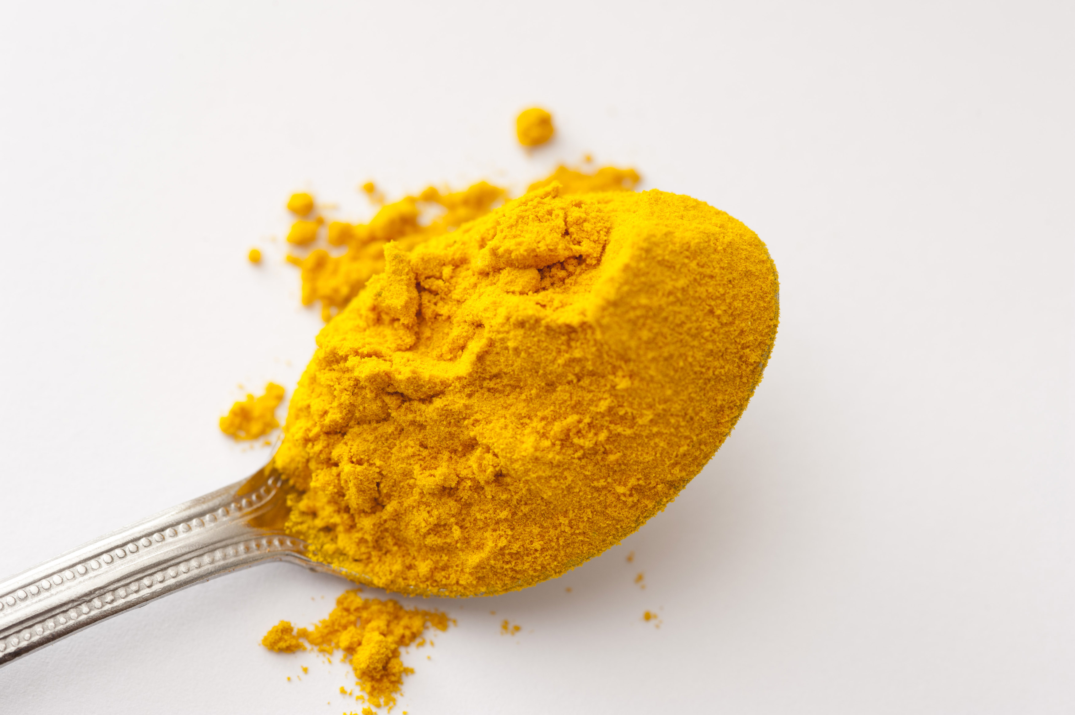 Silver teaspoon heaped with ground dried turmeric powder over a white background with copy space