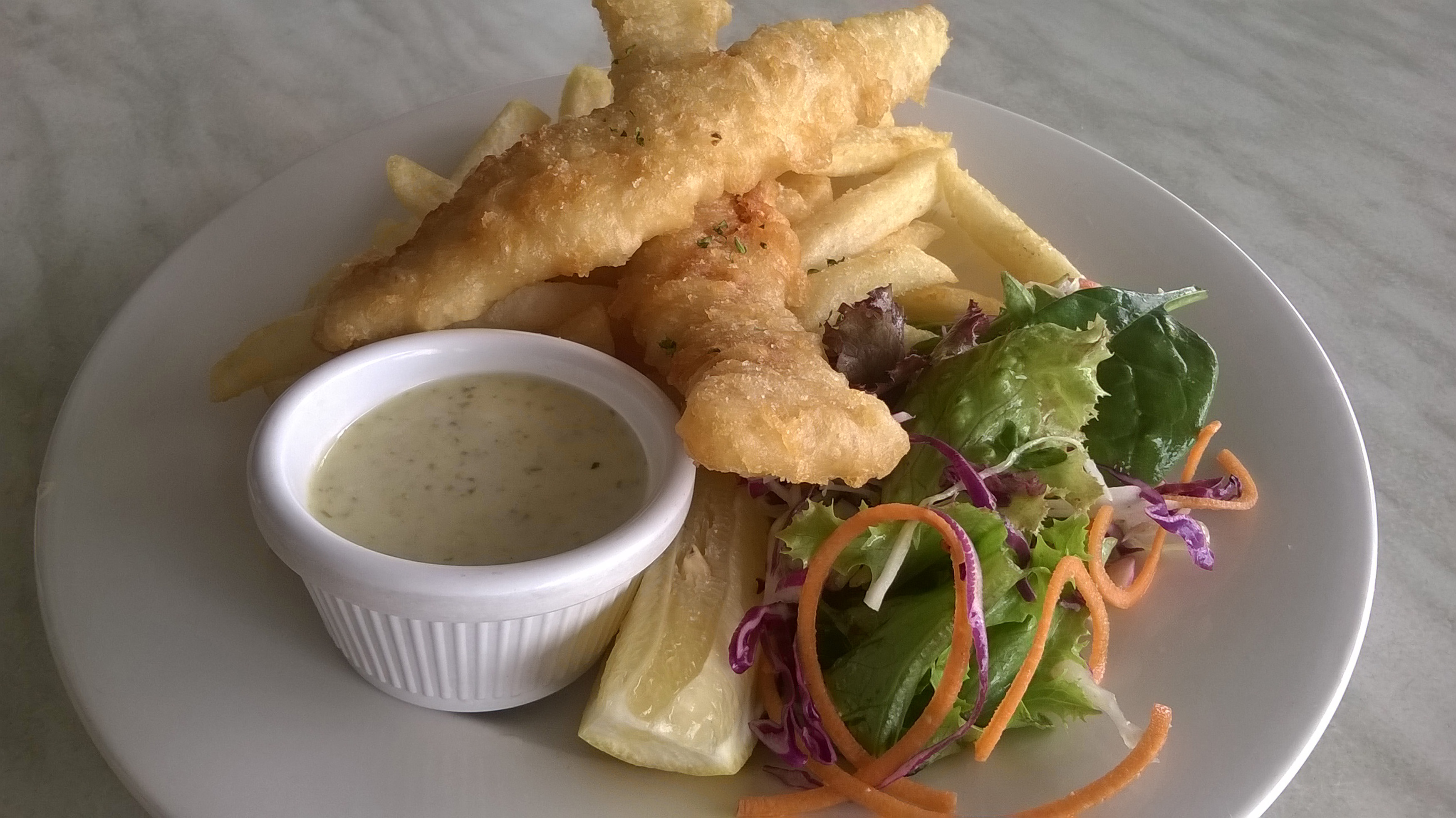 Battered fish and fried potato chips served with a savory sauce and a fresh salad on a white plate, close up high angle view